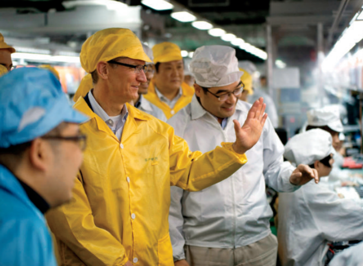 Cook, in yellow, visits a Foxconn facility in Henan Province, China, where iPhones are produced.