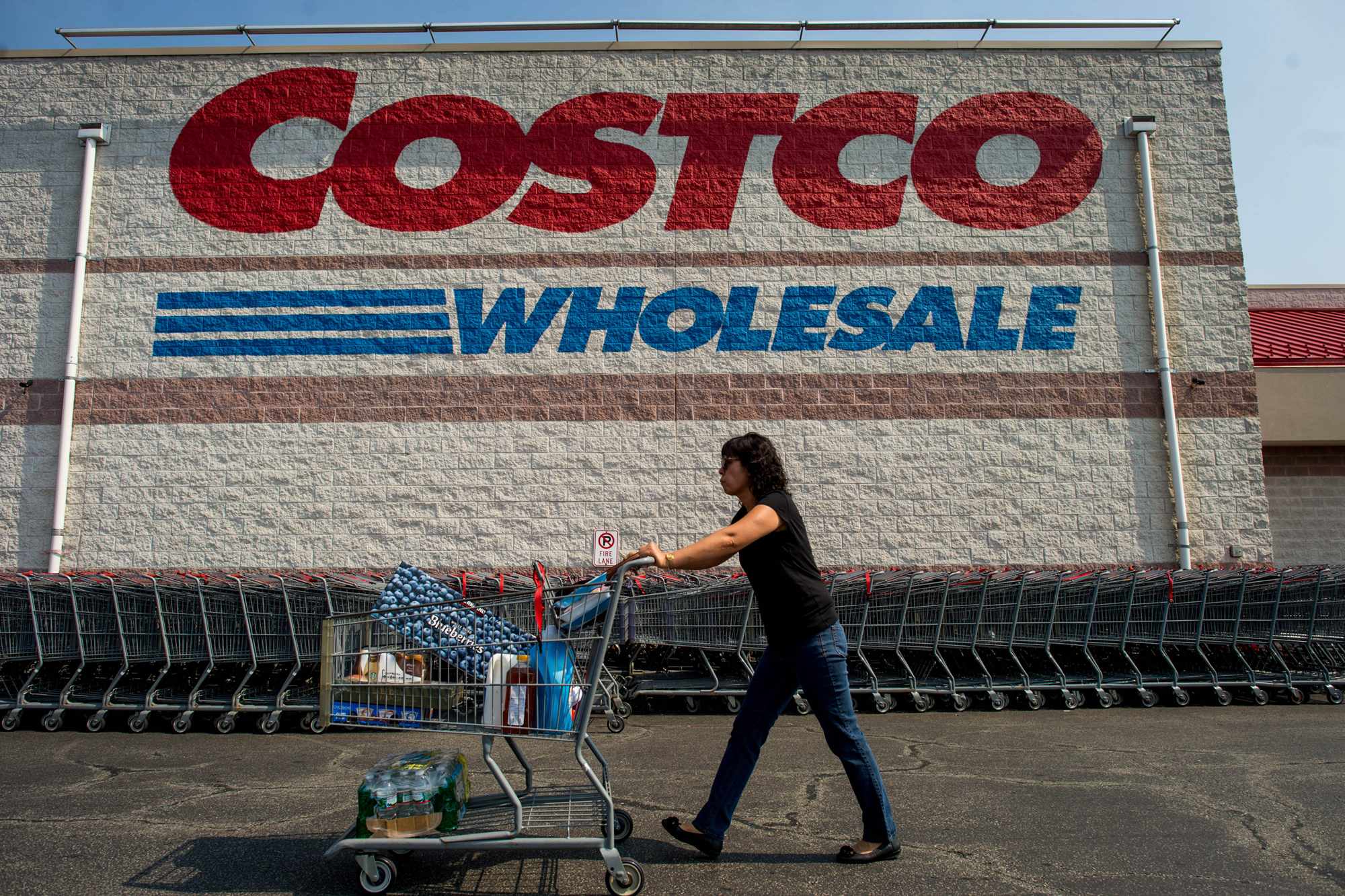 A woman pushes her grocery cart past a Costco.