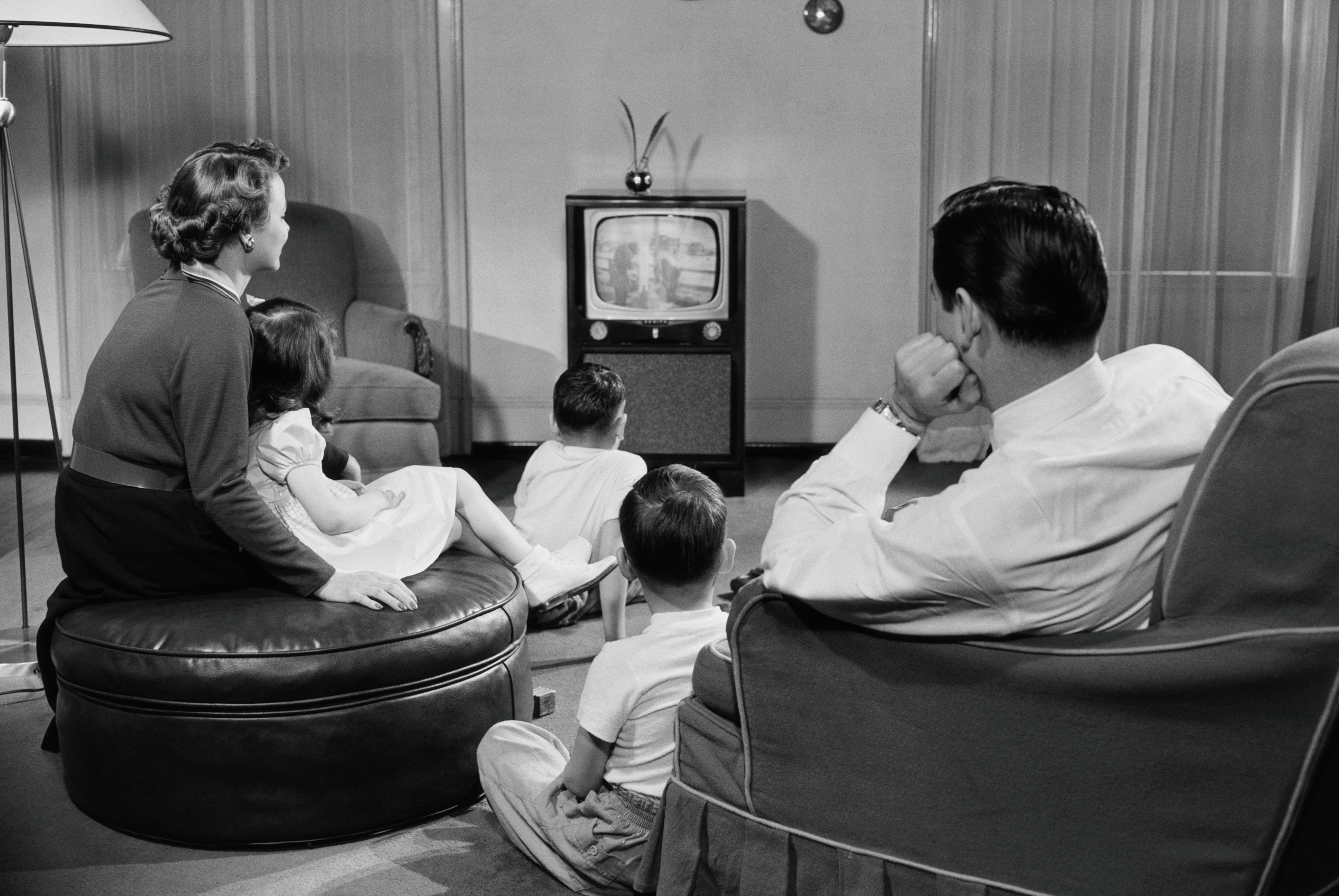 A family watches TV in the living room in the 1950s.