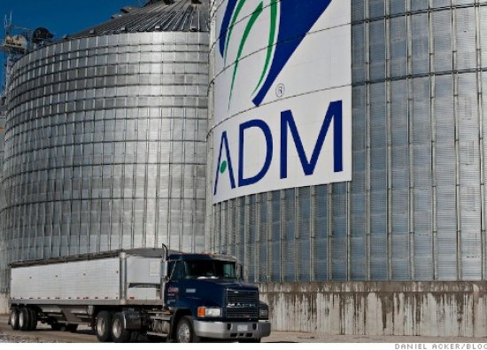 A grain truck passes an Archer Daniels Midland Co. (ADM) logo on the side of a grain storage bin at an ADM grain elevator in Niantic, Illinois, U.S., on Tuesday, Nov. 12, 2013. Photographer: Daniel Acker/Bloomberg