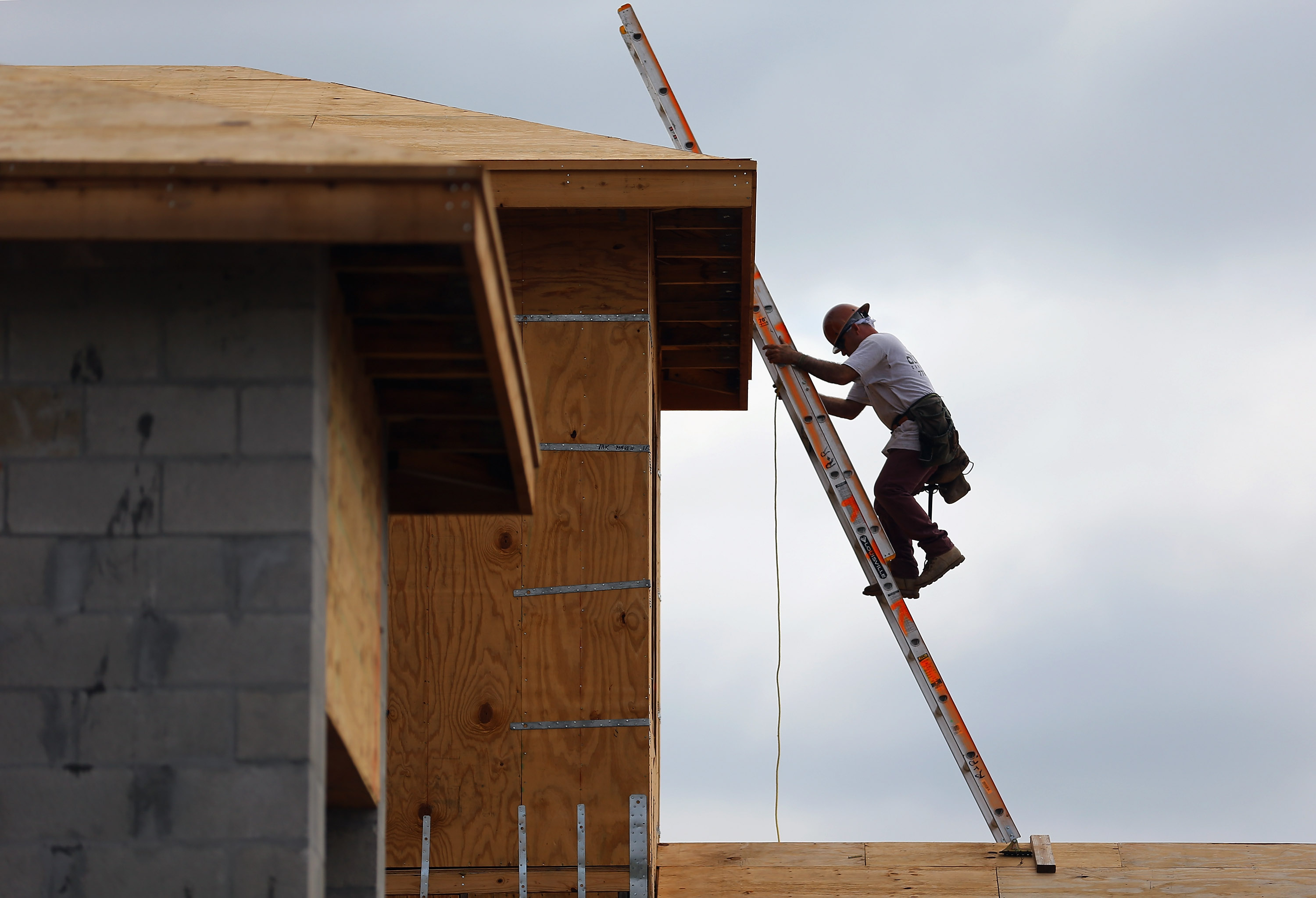 A construction worker climbs on the roof of a home.