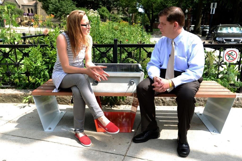Sandra Richter, left, and Mayor Walsh discuss new technology while sitting on the Soofa in Titus Sparrow Park in Boston.