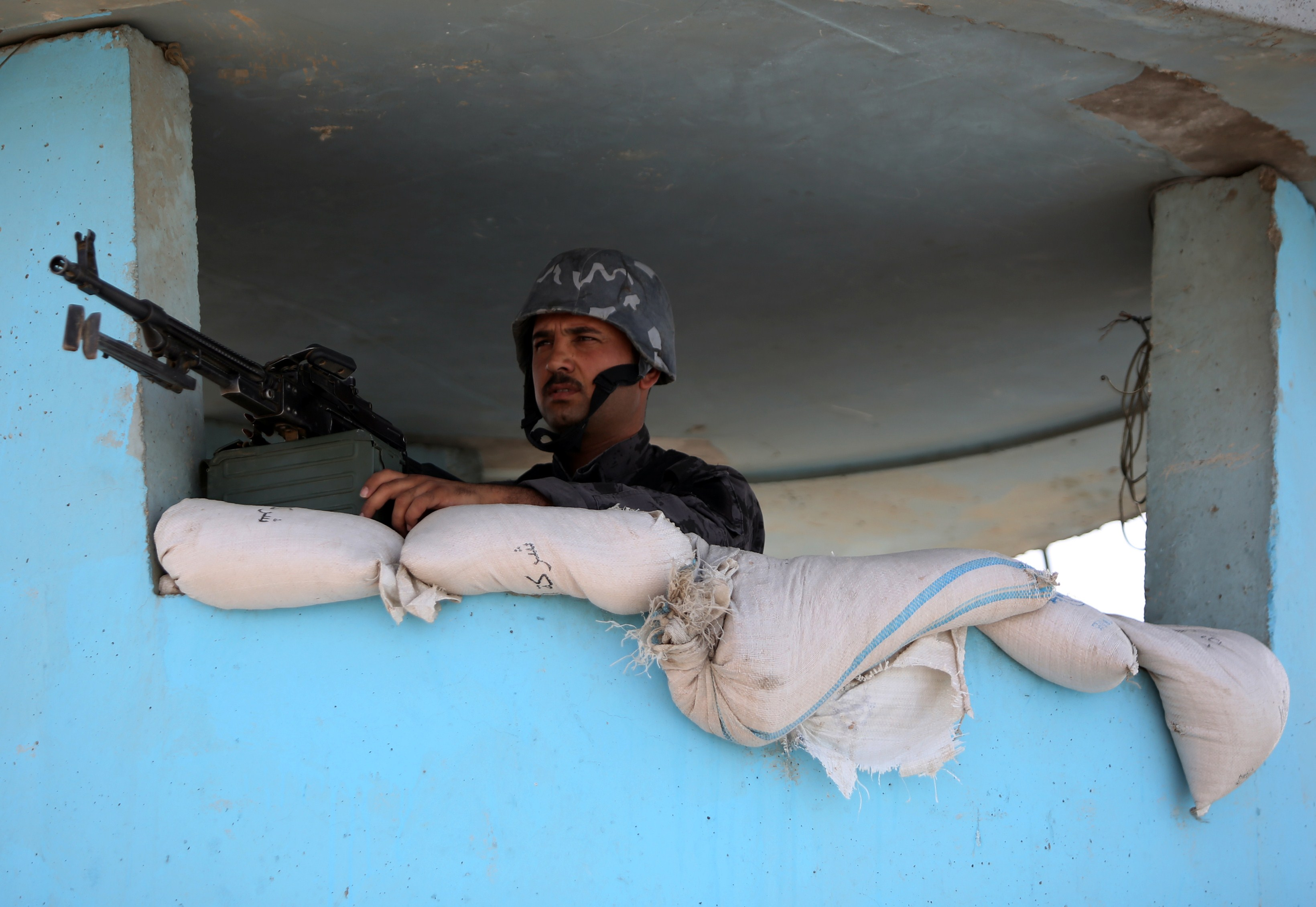 Waiting for ISIL: An Iraqi policeman on the outskirts of Baghdad.
