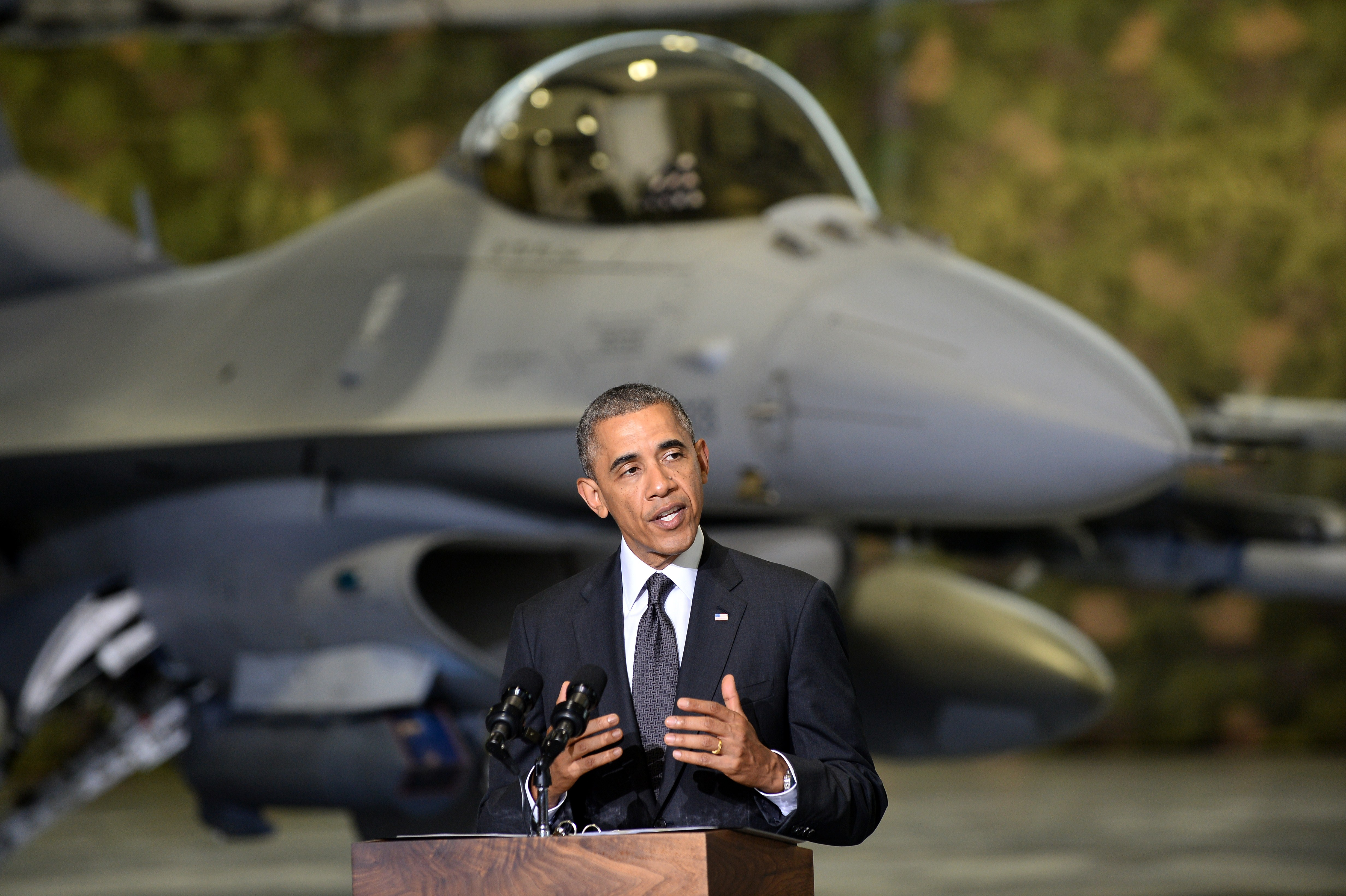 President Barack Obama addresses U.S. and Polish airmen in front of an F-16 fighter jet in a hangar at Warsaw.