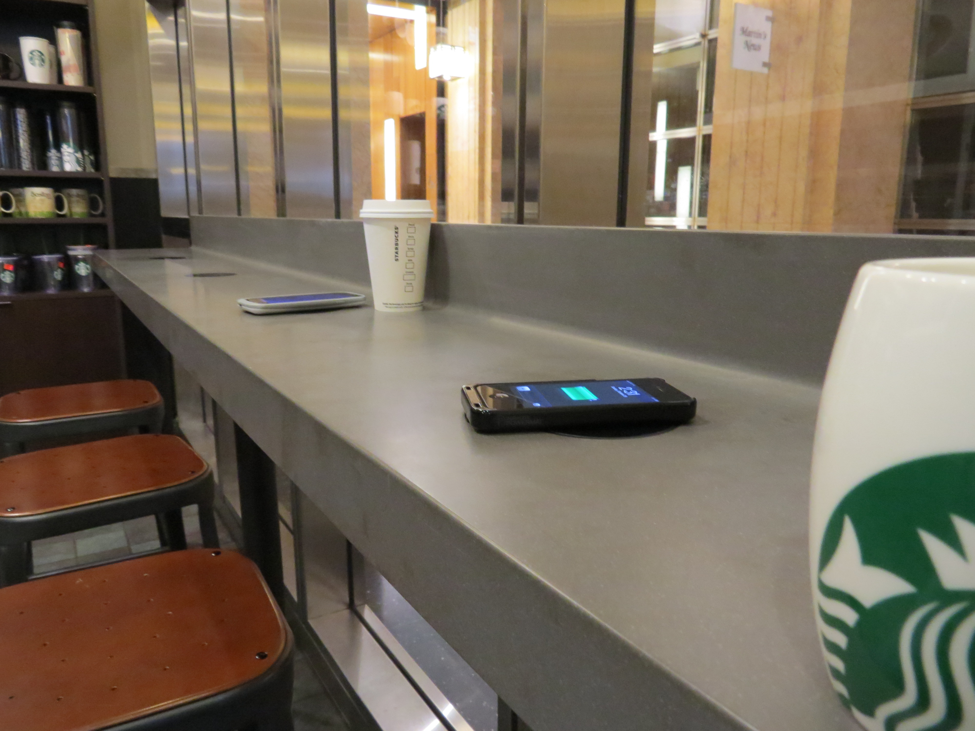 A phone being charged wirelessly at Starbucks