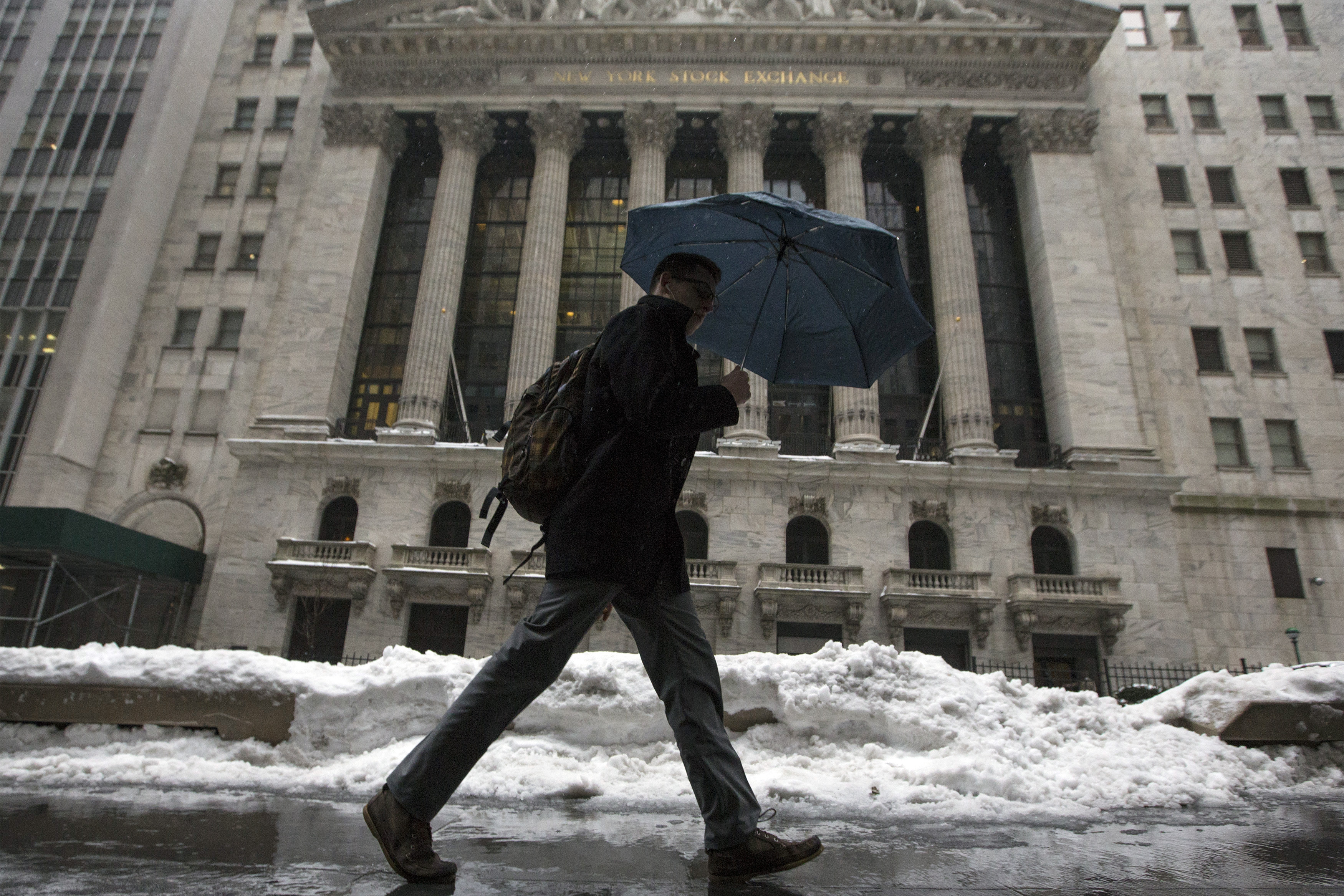 A man walks past the New York Stock Exchange in New York's financial district
