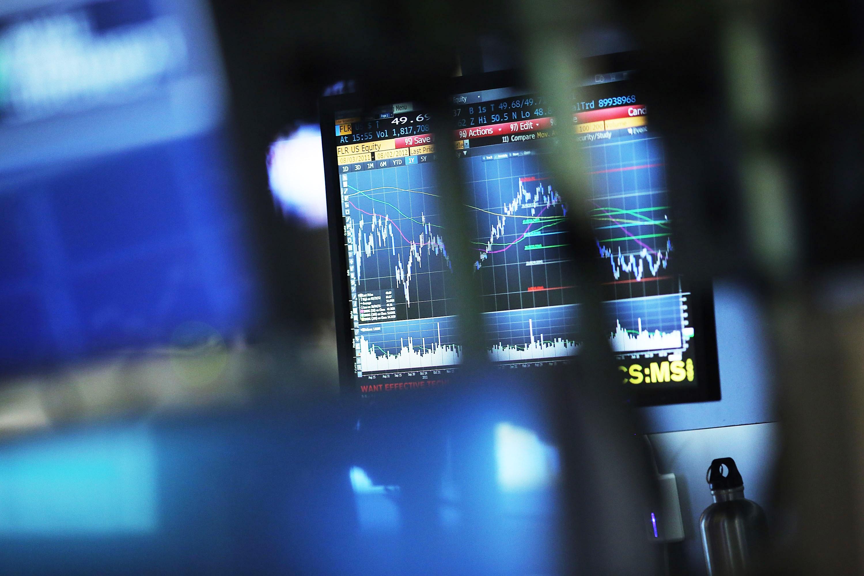 A monitor displays market graphics.