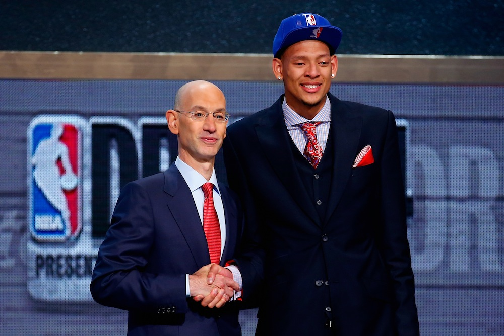 Isaiah Austin of Baylor (R) shakes hands with NBA Commissioner Adam Silver