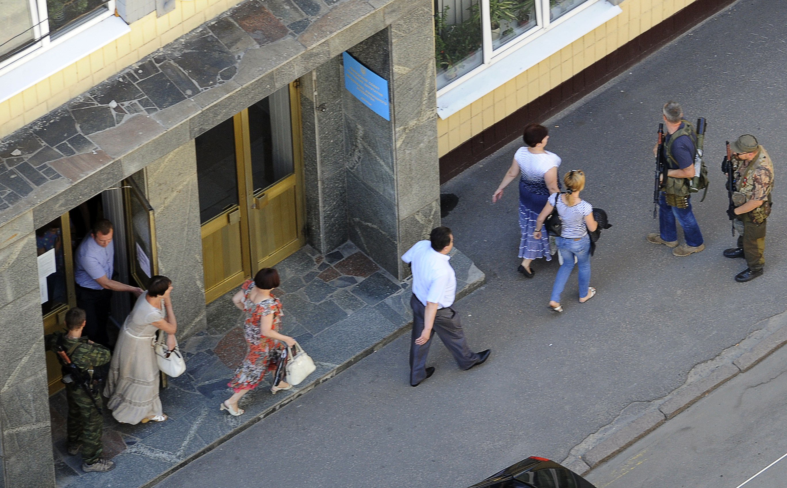 Employees leave their offices escorted by pro-Russian militants occupying the building for sniper positions in the centre of the eastern Ukrainian city of Donetsk on July 1, 2014.