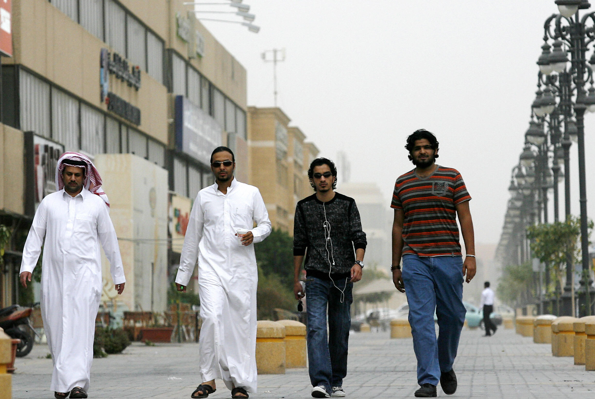 Saudi youths walk together in a business