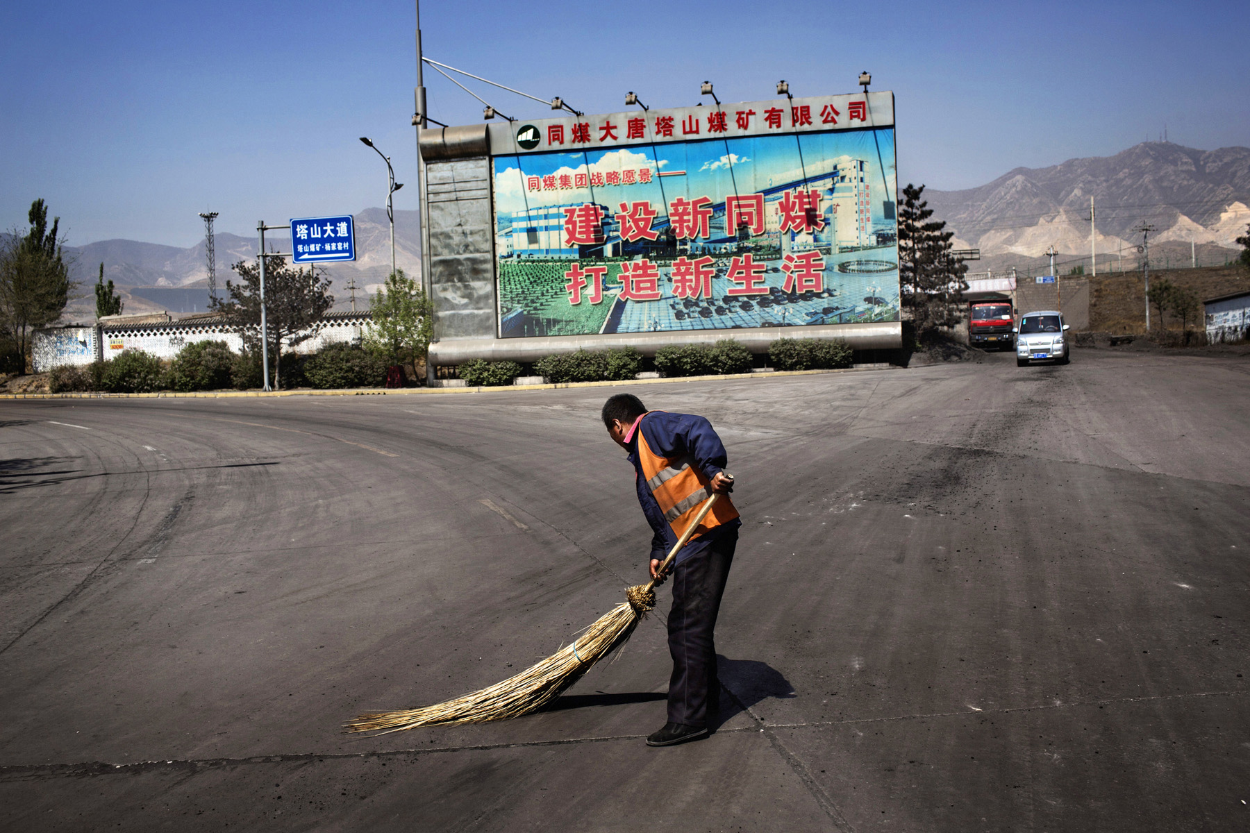 A worker sweeps coal dust in front of a billboard