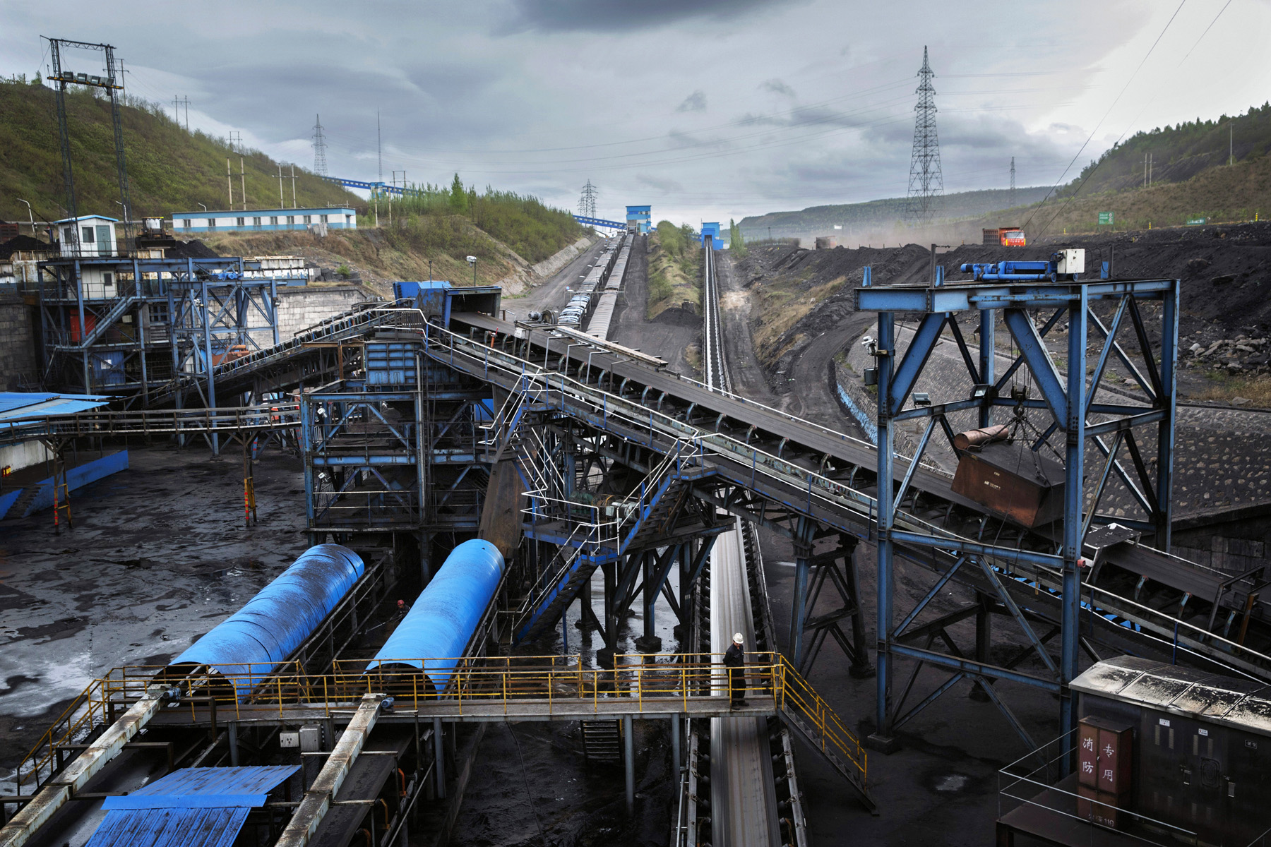A worker looks over a conveyor moving coal through the An Tai Bao open pit coal mine