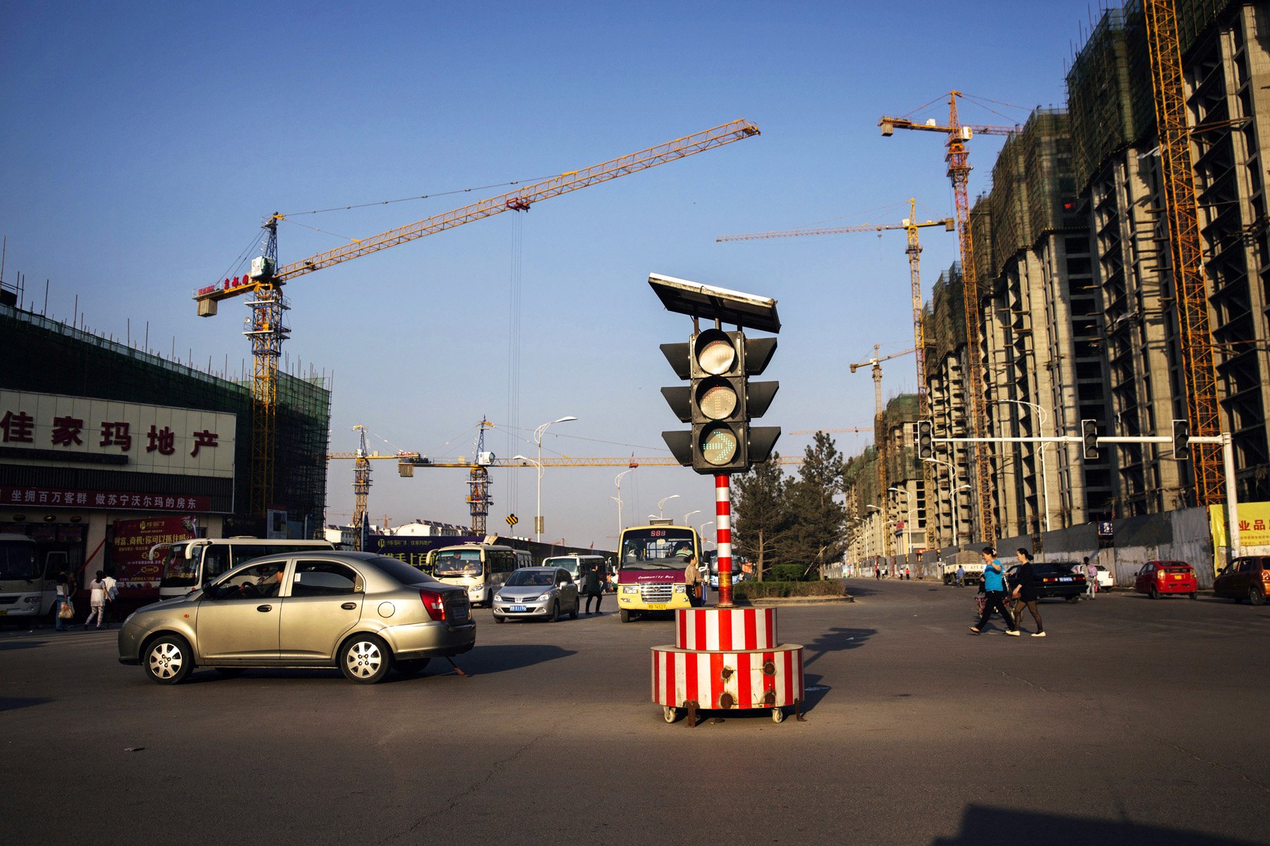 Traffic is seen in front of a construction site in New Ping Wang