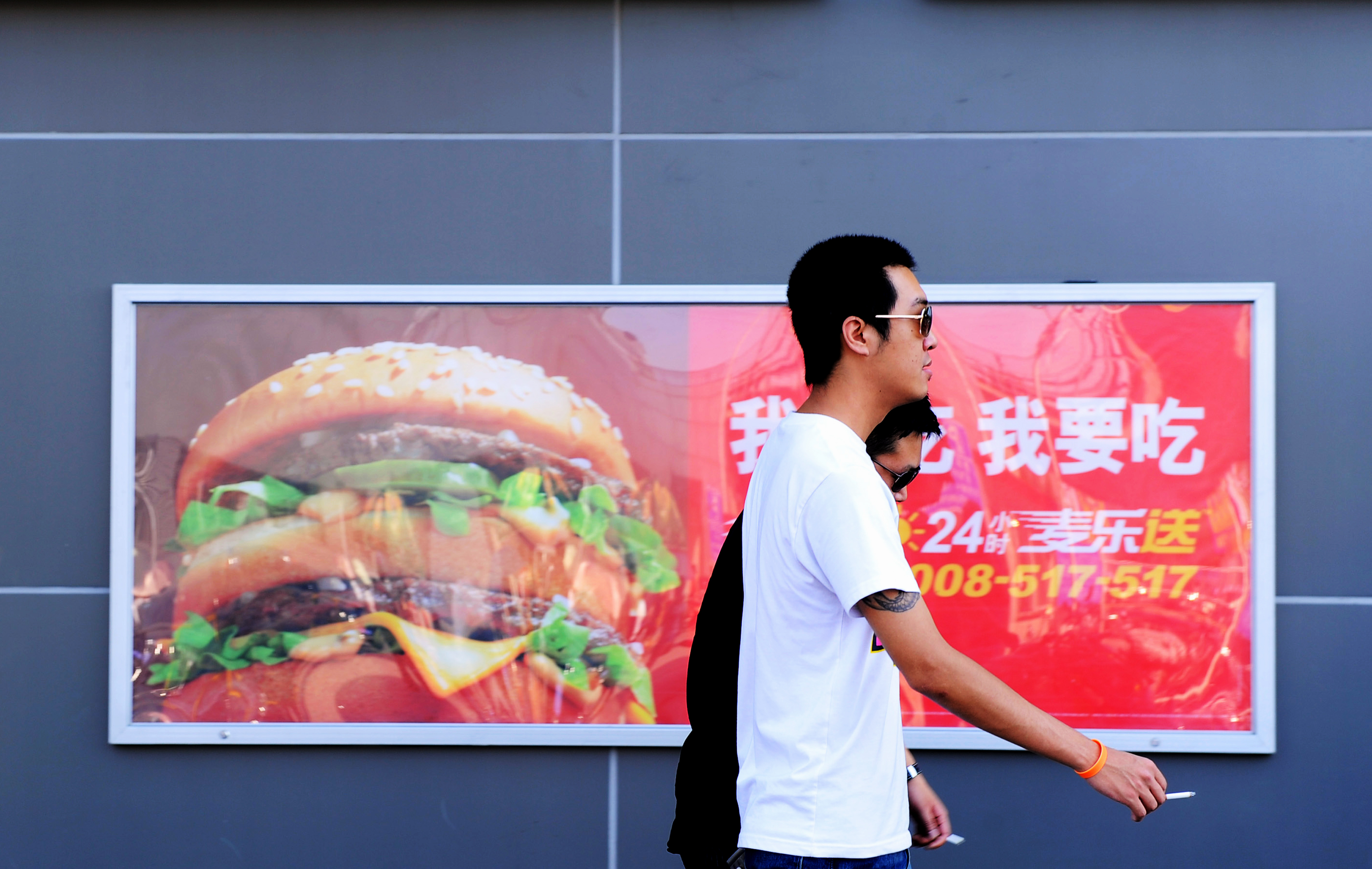 Two Chinese men walk past a billboard ad
