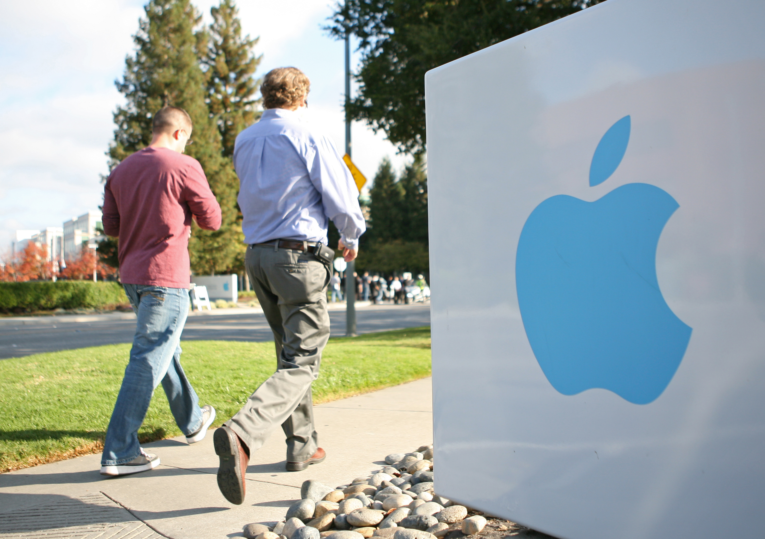 Apple employees walk towards the Apple H
