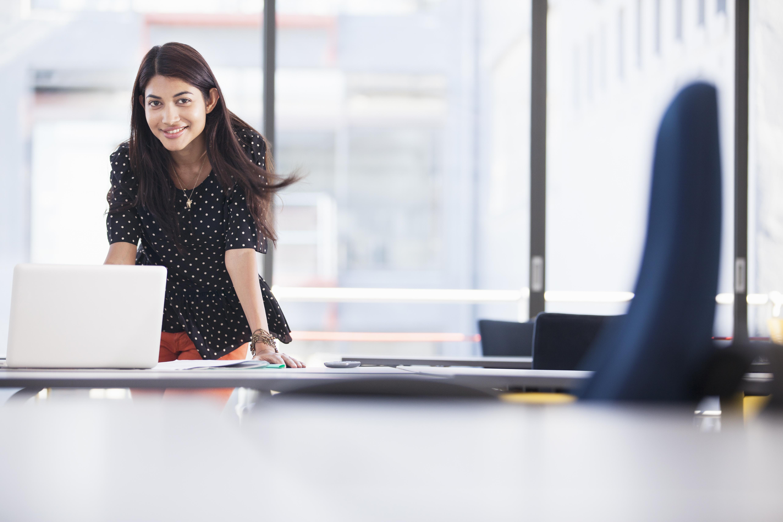 Businesswoman using laptop in modern office