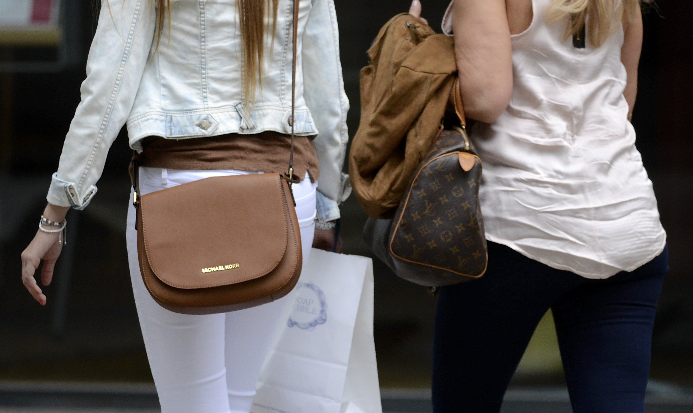 A woman carrying a Michael Kors handbag.