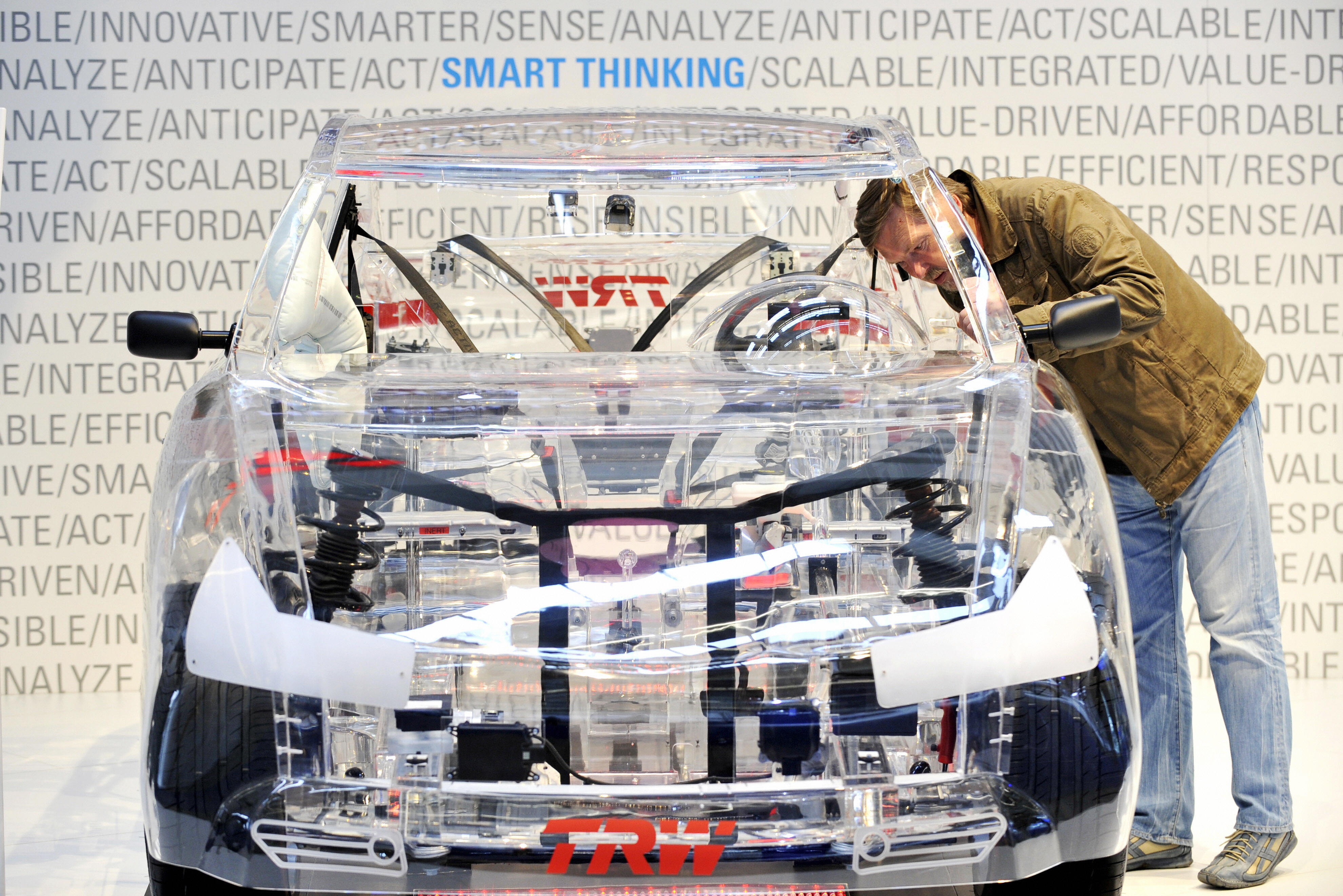 A trade fair visitor looks at a car with