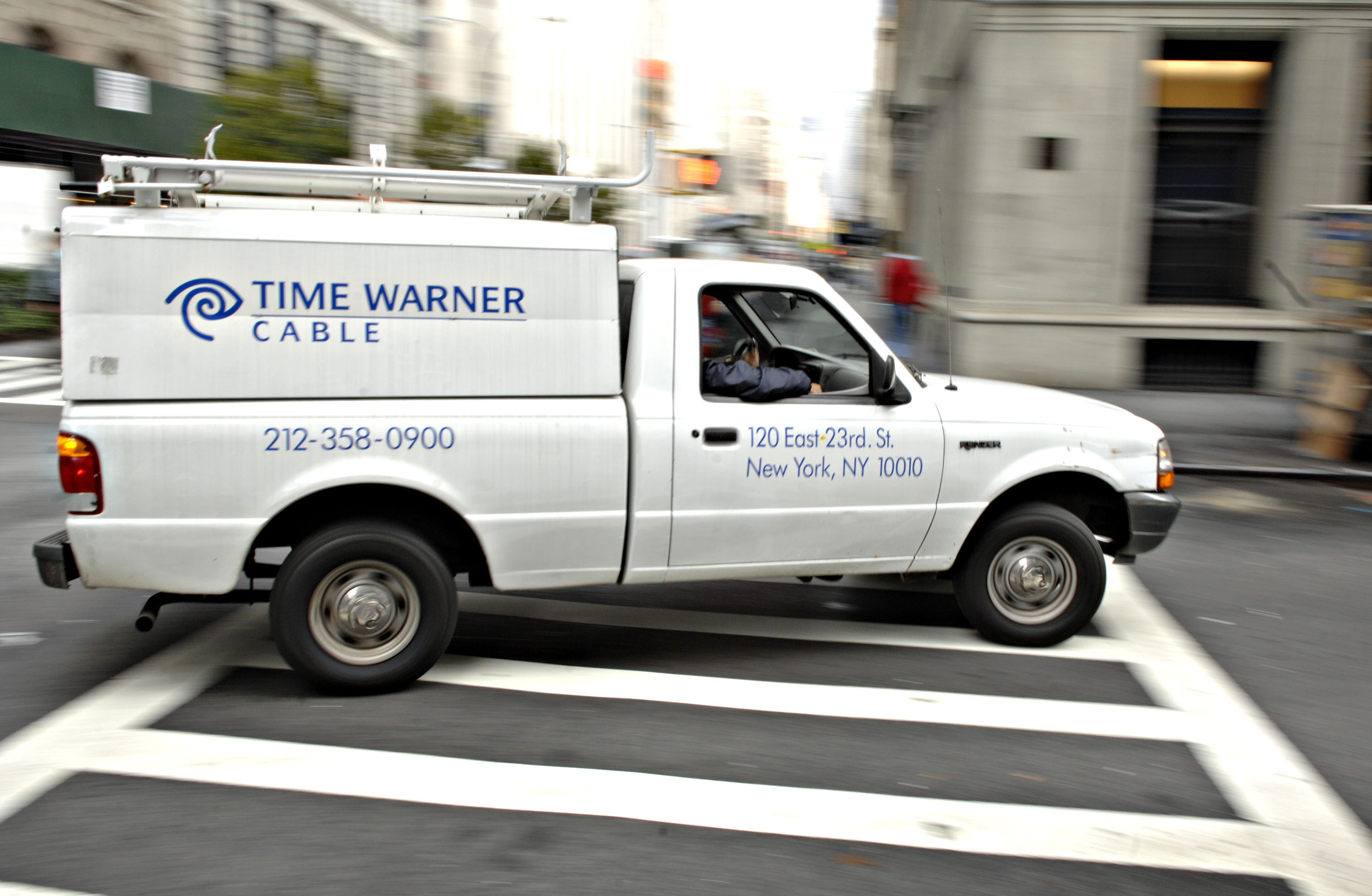 A Time Warner Cable trucks turns a corner on a New York stre