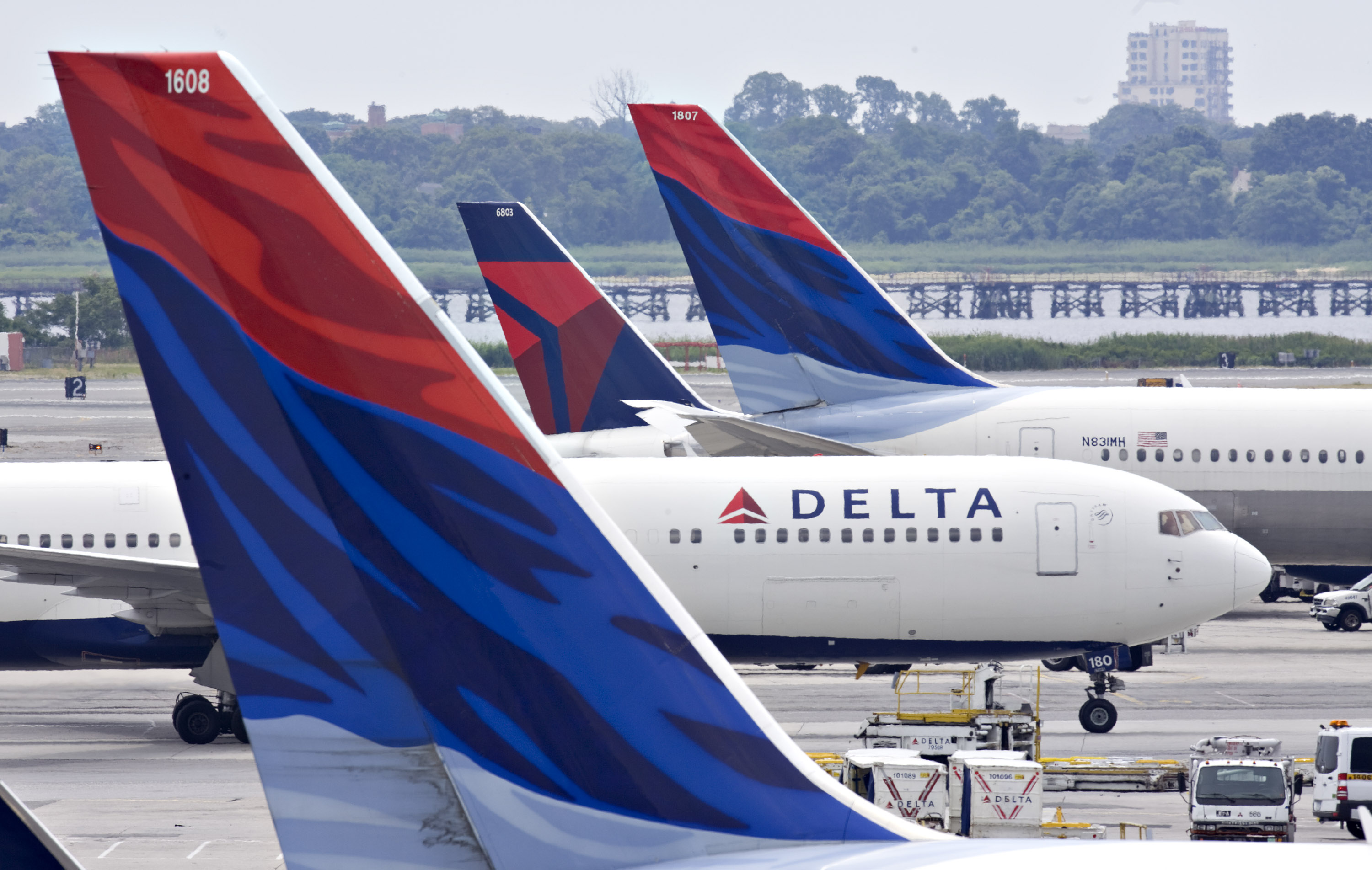 A Delta Air Lines plane taxis toward a gate between other De