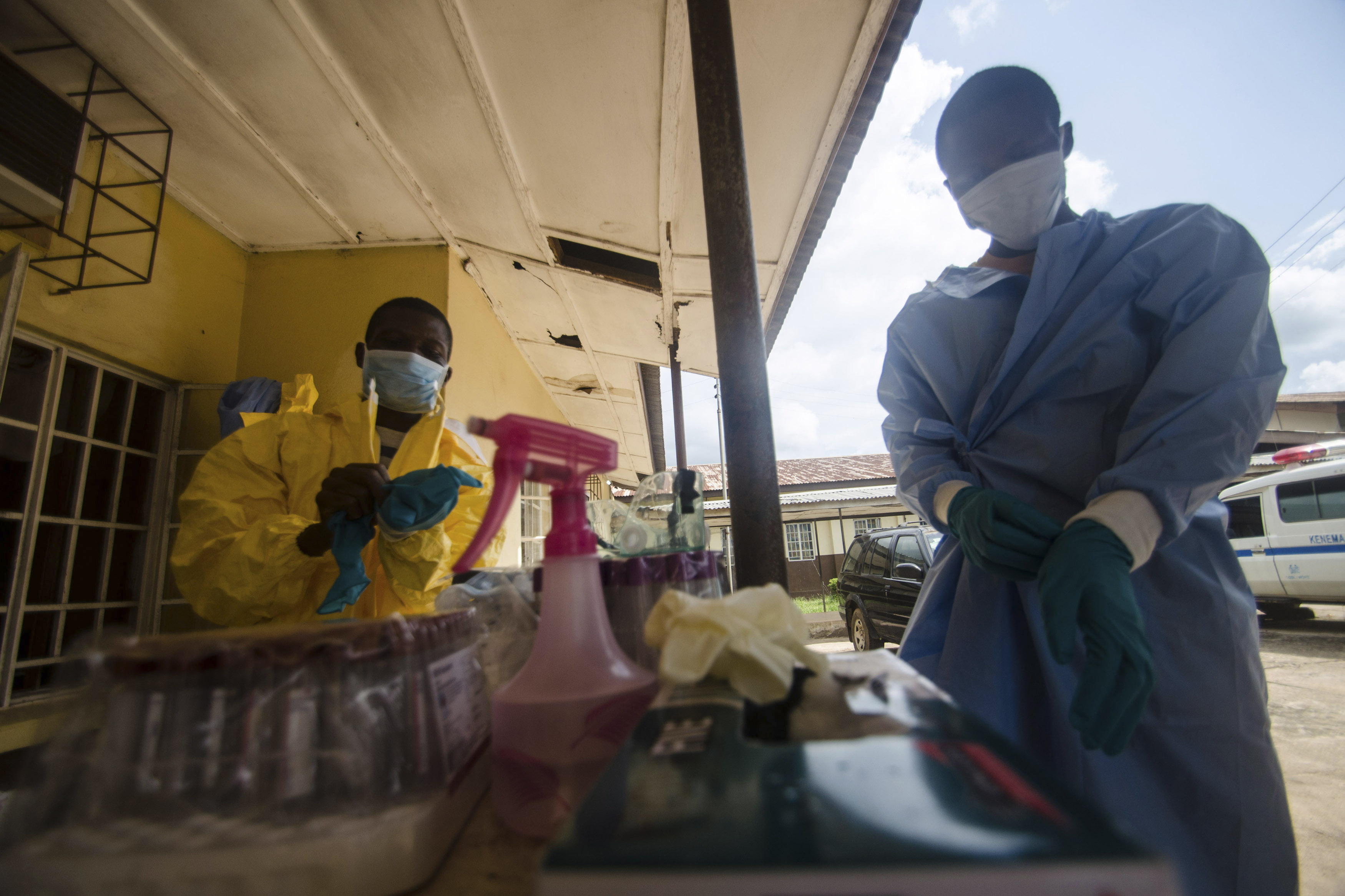 Medical staff put on protective gear in Kenema government hospital before taking a sample from a suspected Ebola patient in Kenema