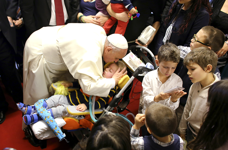 "Pope Francis kisses a child during his pastoral visit at the parish church "" Santa Maria dell'Orazione"" at Setteville di Guidonia neighborhood of Rome"