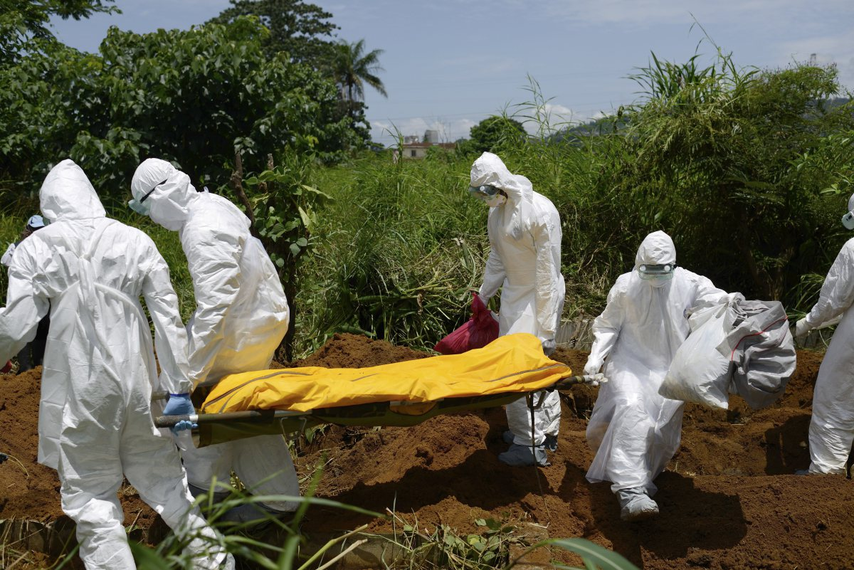 Members of a burial team wearing protective suits bury an Ebola victim in Freetown, Sierra Leone.