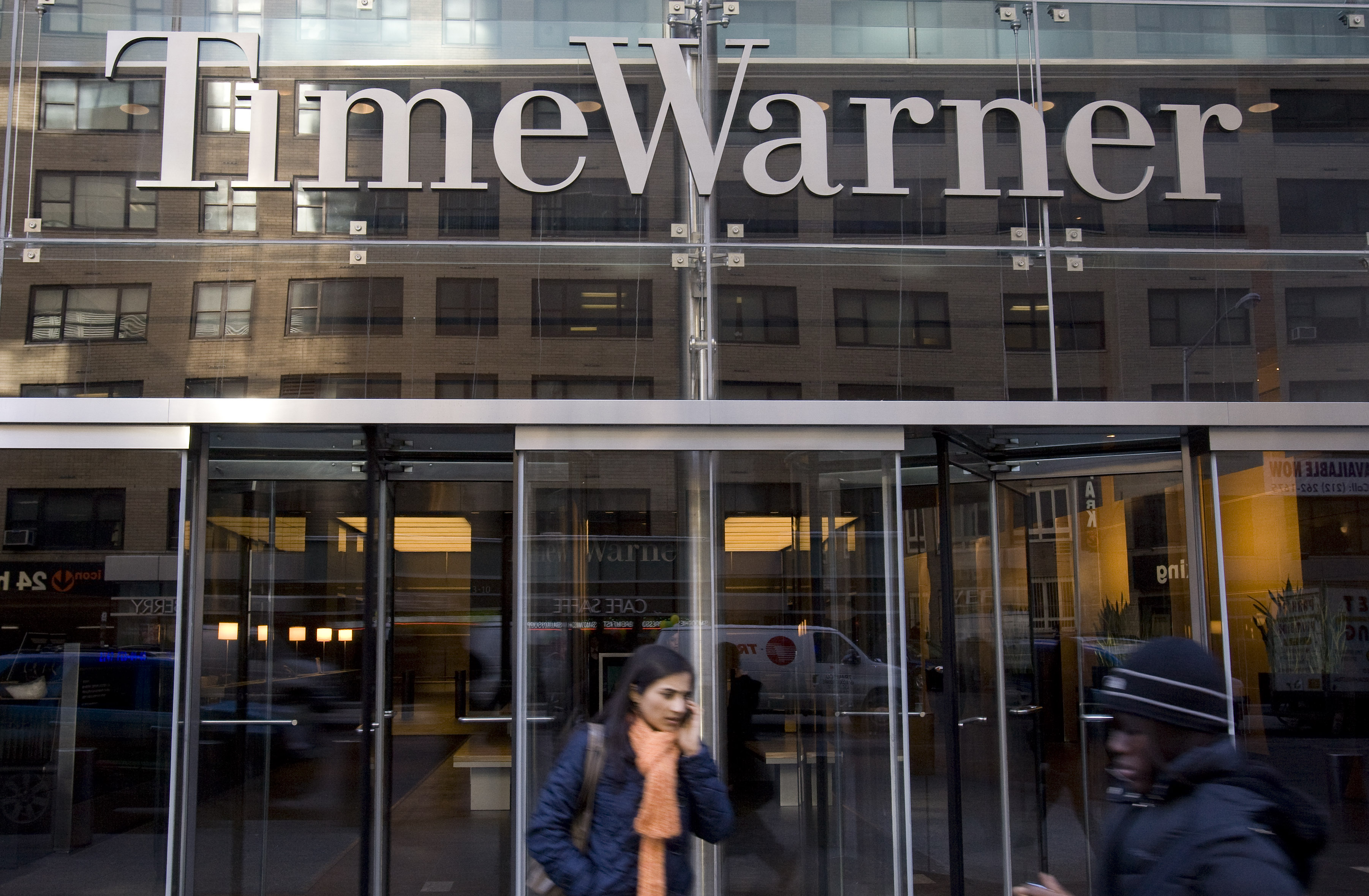 Pedestrians walk past the headquarters of Time Warner Inc. i