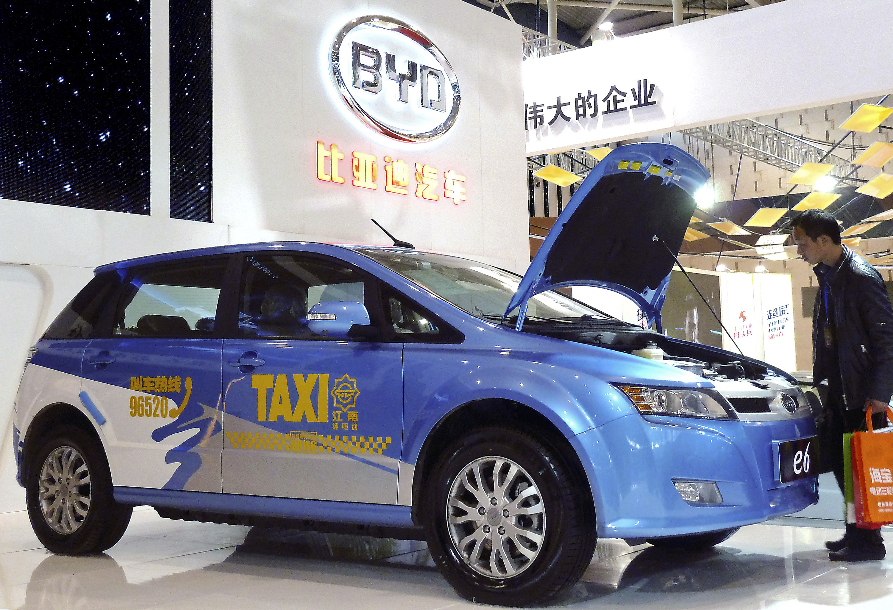 A visitor looks at BYD E6 electric car on display at the New Energy Auto Expo in Nanjing