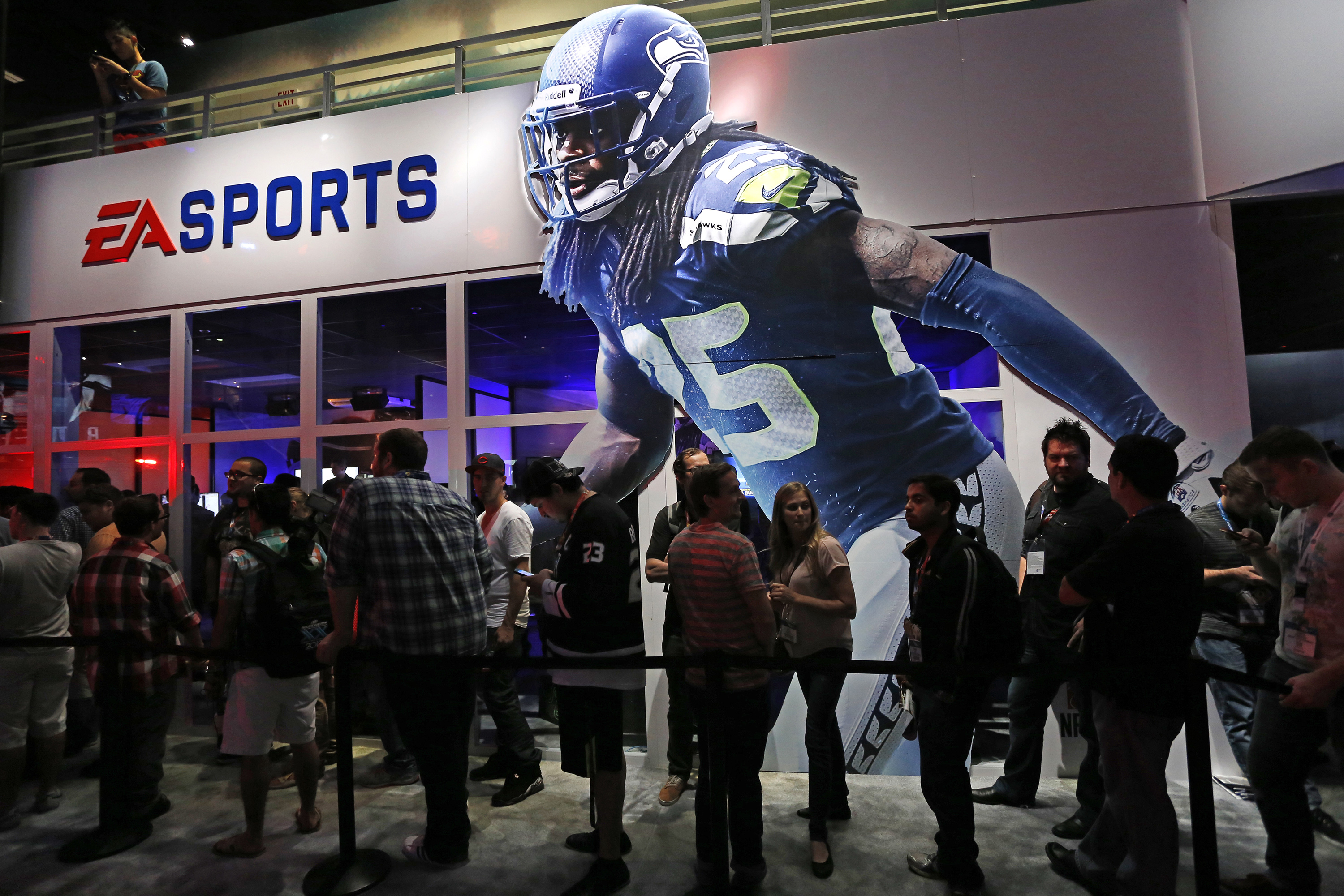 """People wait in-line under """"Madden NFL 15"""" billboard with an image of NFL player Sherman at the Electronic Arts booth during the 2014 Electronic Entertainment Expo, known as E3, in Los Angeles"""