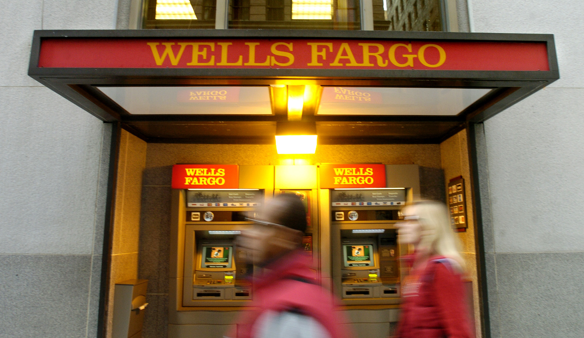 Pedestrians pass an ATM outside Wells Fargo & Co.'s San Fran