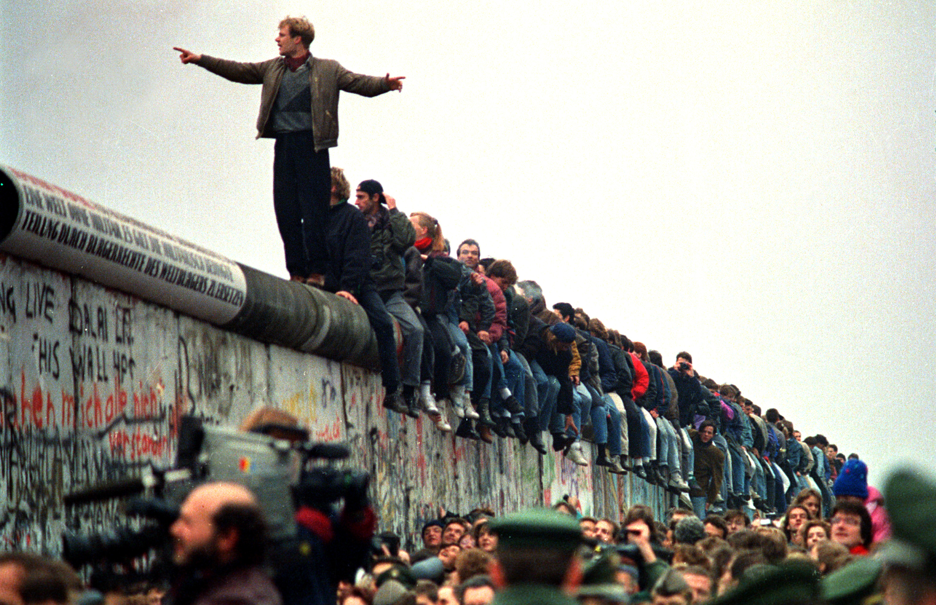 People Stand On The Berlin Wall