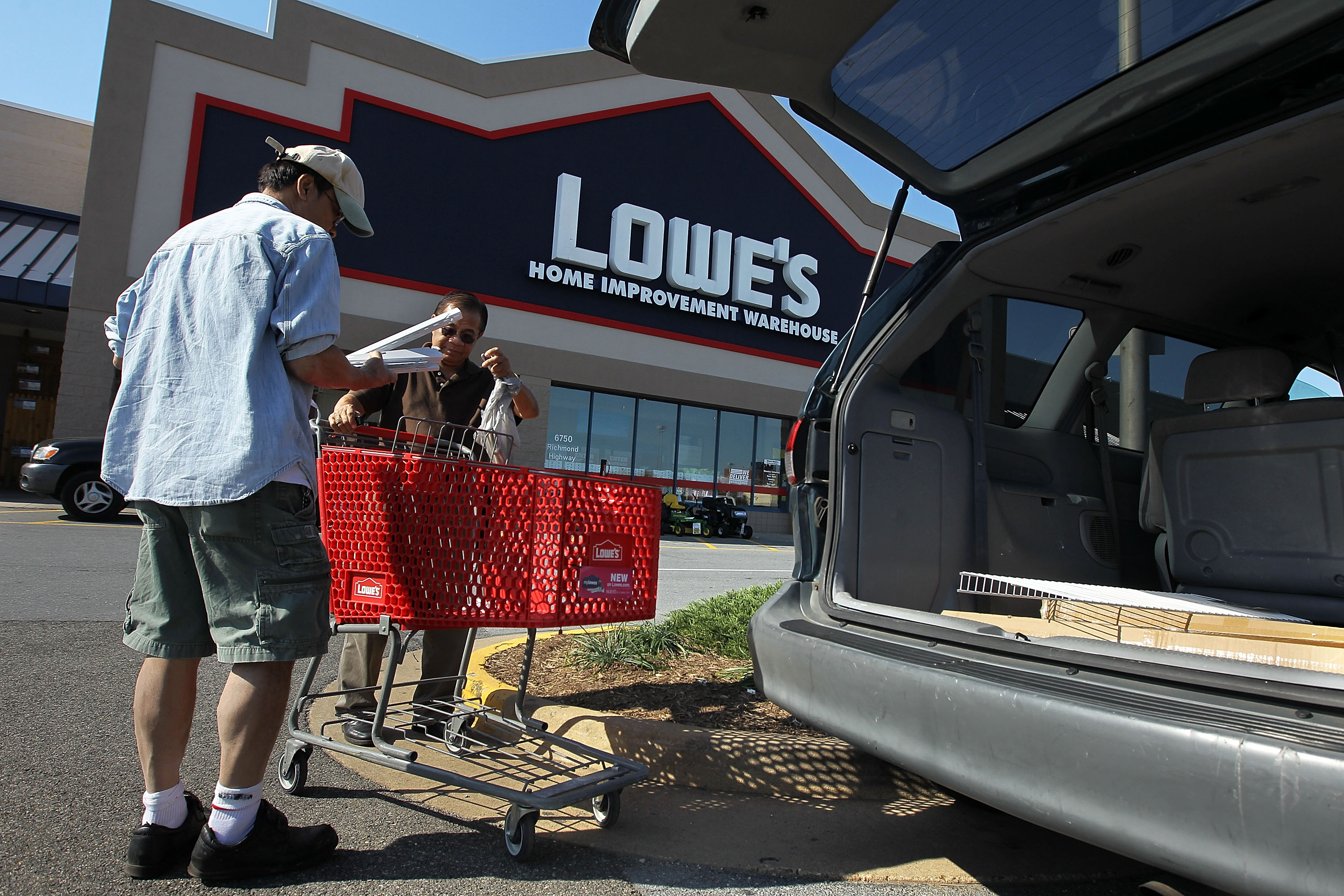 Customers load their purchases into a vehicle outside a Lowe's store in Alexandria, Va.
