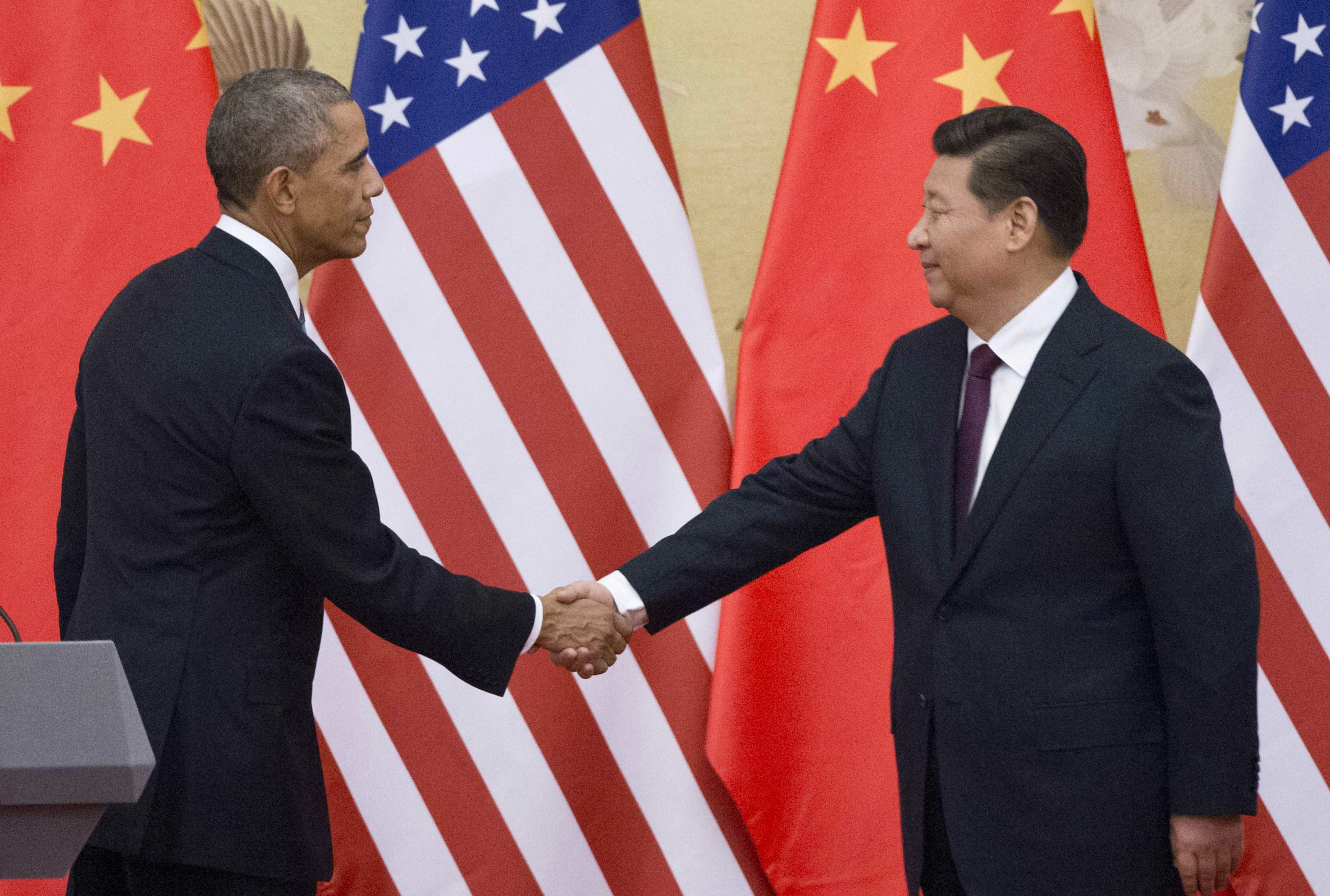 US President Barack Obama (L) and China's President Xi Jinping shake hands following a bilateral meeting  at the Great Hall of the People in Beijing on November 12, 2014.