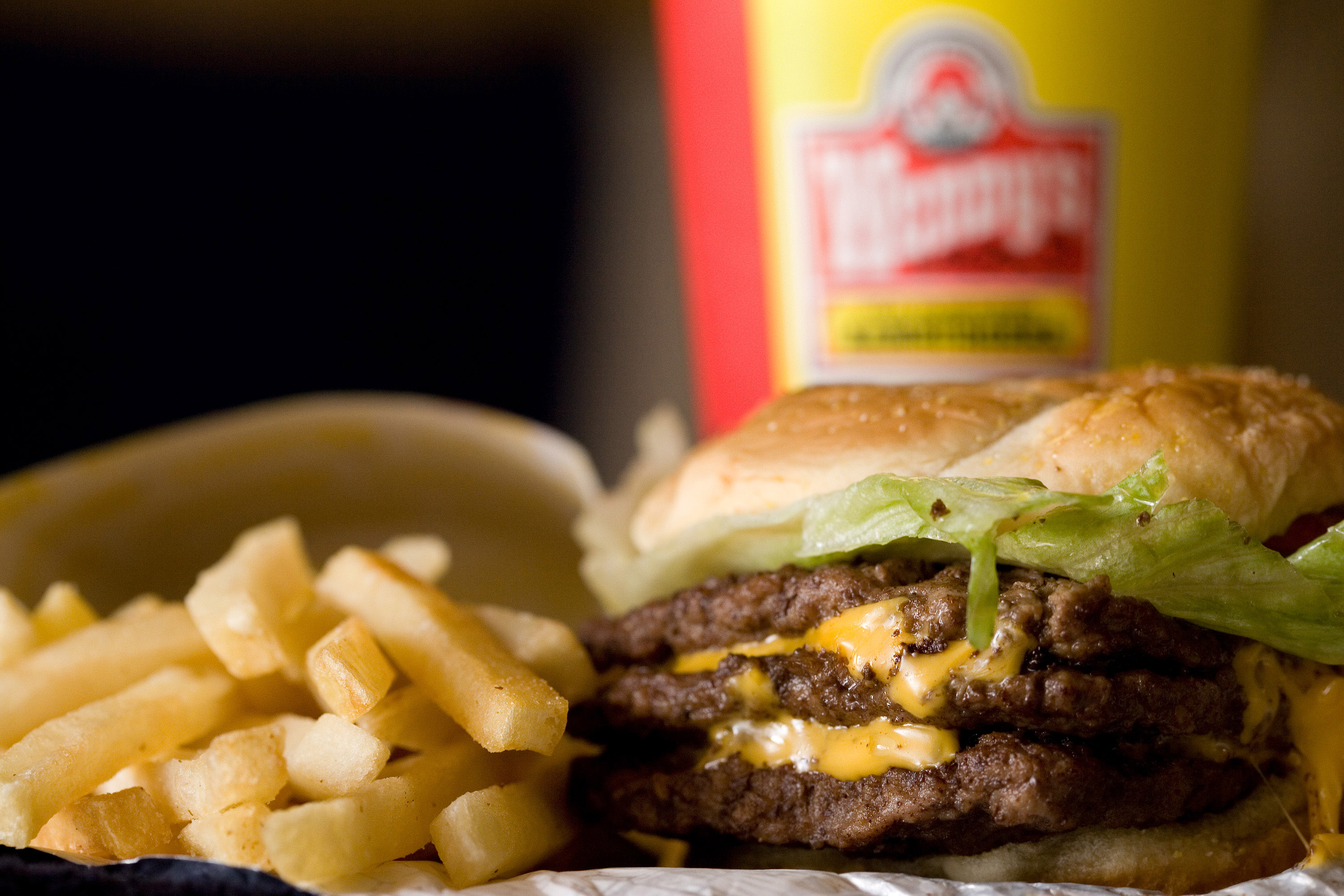A triple cheeseburger combo is arranged for a photograph in