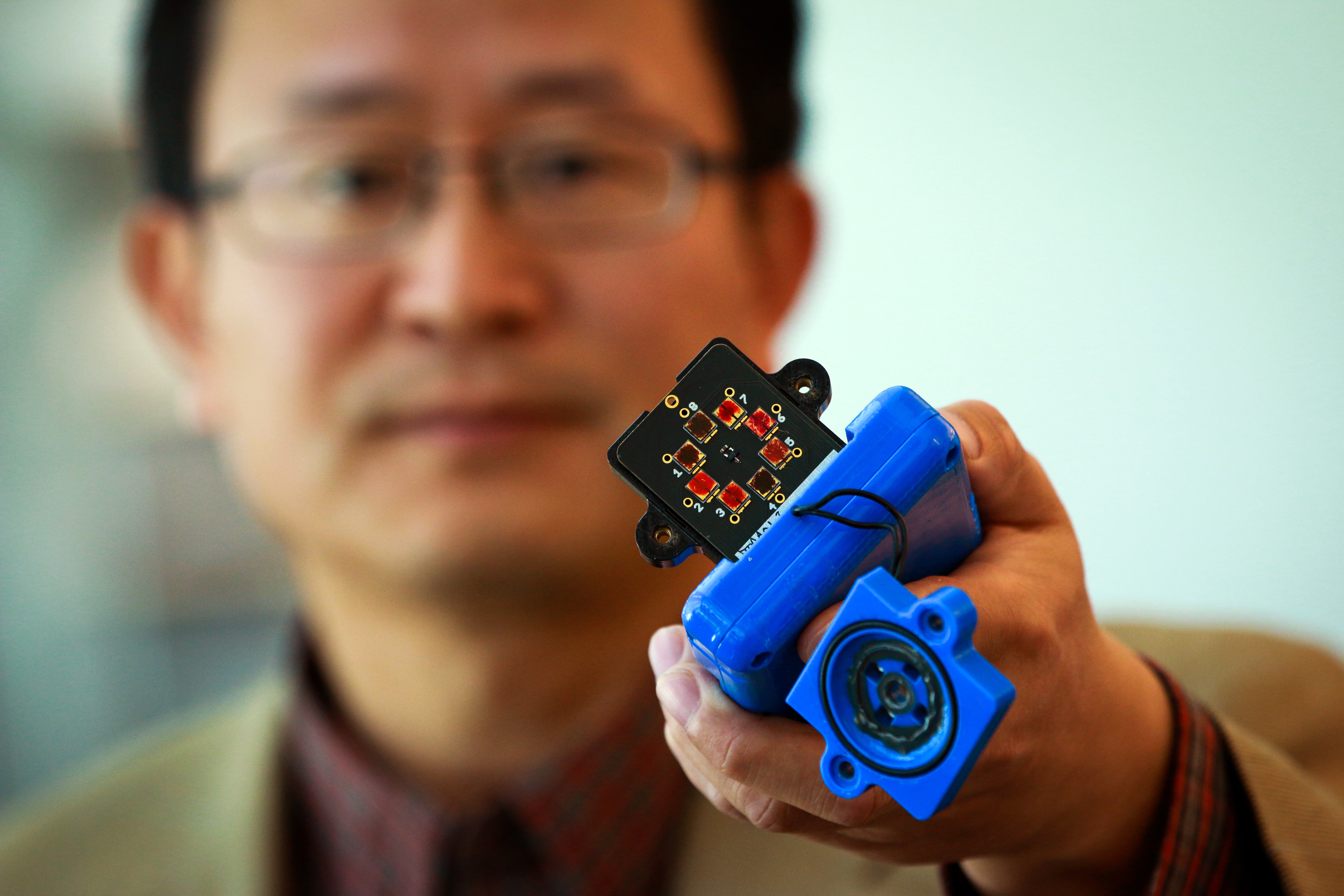 Ling Zang holds a prototype device outfitted with his newly-developed carbon nanotube material that can detect explosives, toxic chemicals and illegal drugs