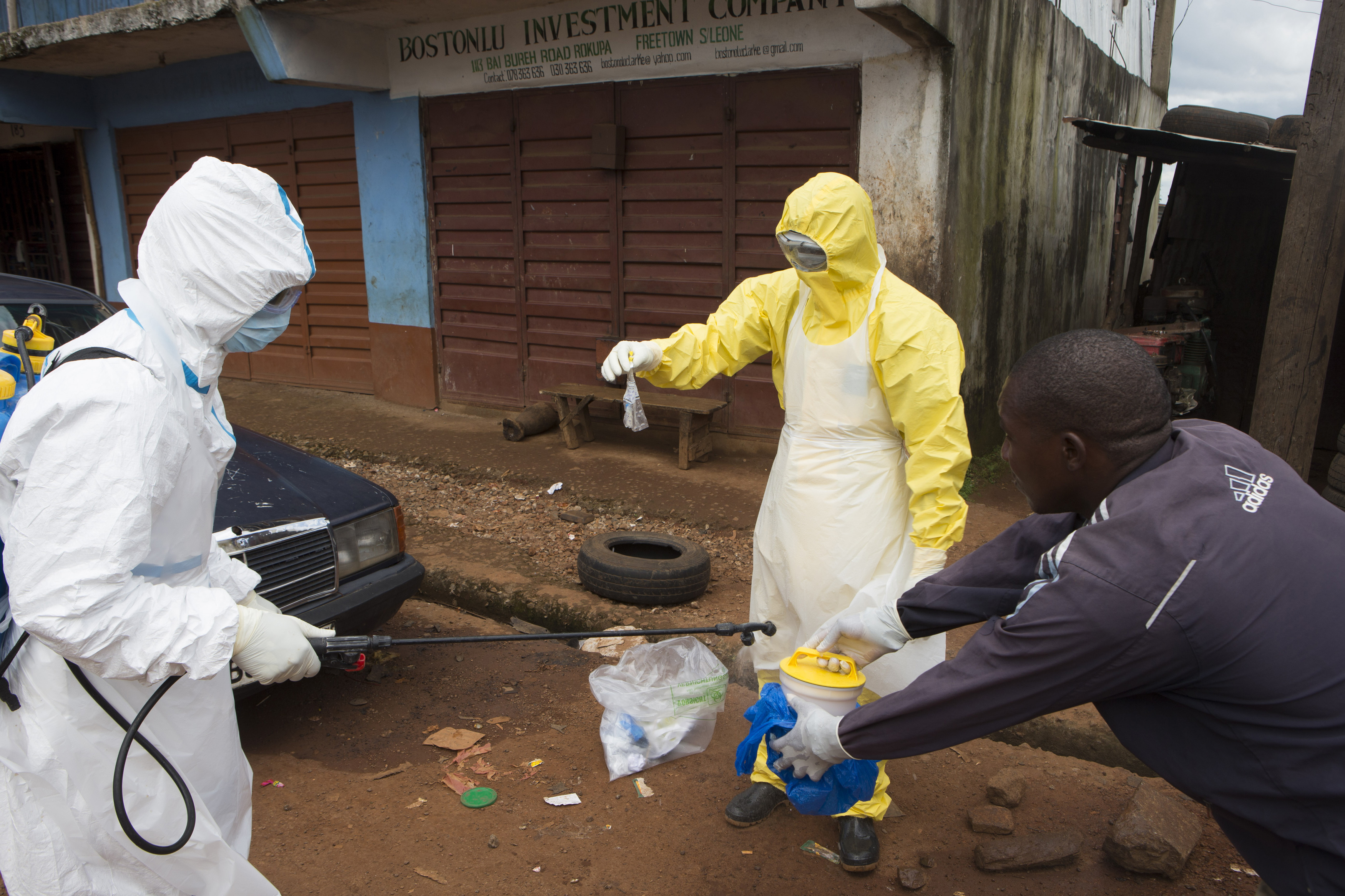 Health workers in protective equipment handle a sample taken from the body of someone who is suspected to have died from Ebola virus, near Rokupa Hospital