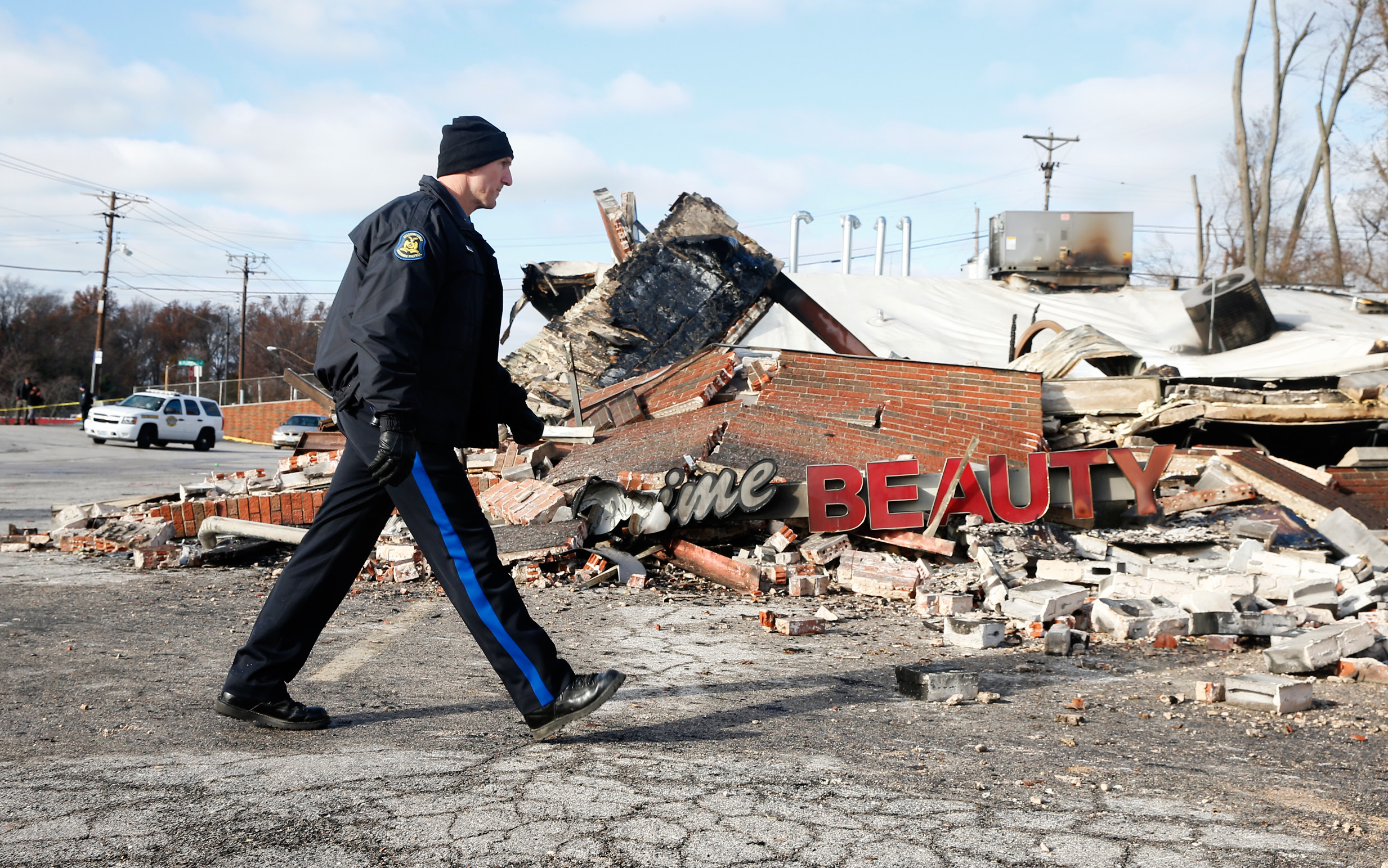 A police officer looks over the site of a building that was burned in riots the previous night in Ferguson