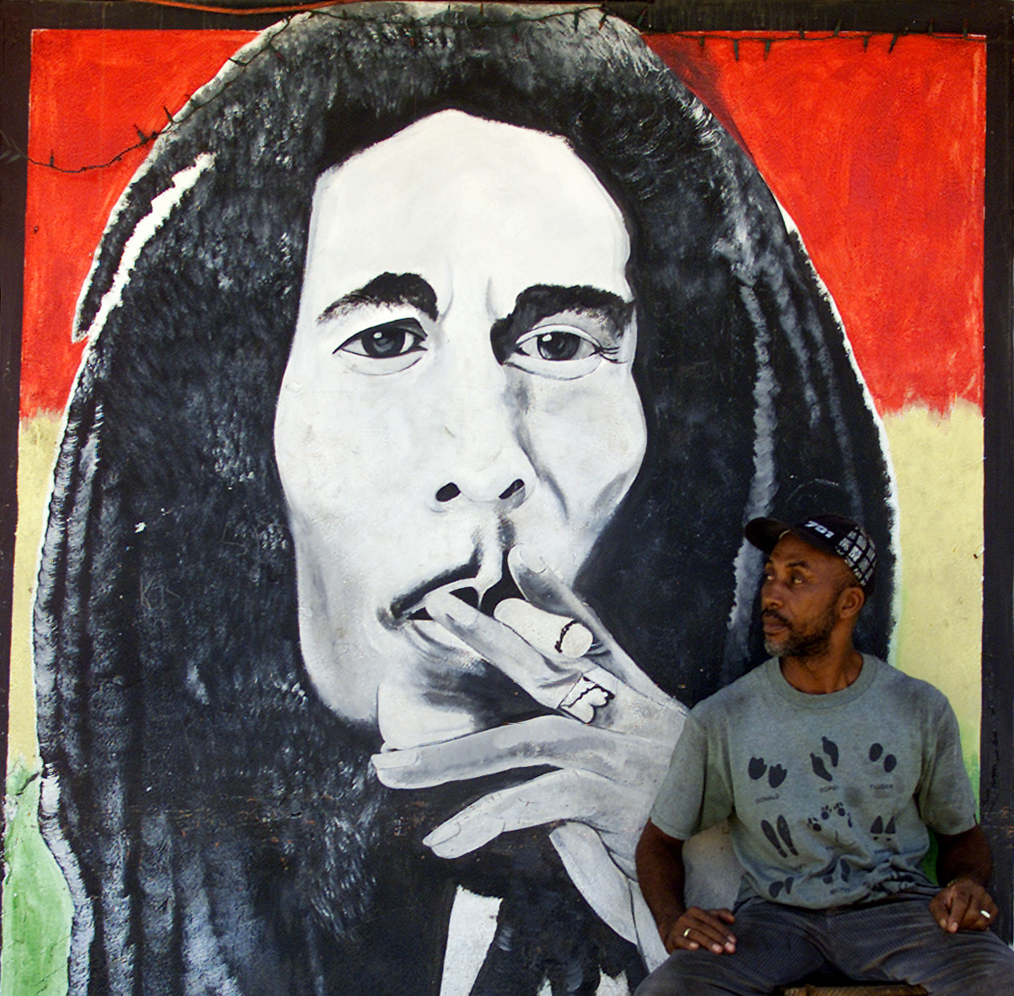 A MAN SITS BY A MURAL OF JAMAICAN REGGAE MASTER BOB MARLEY IN KINGSTON.