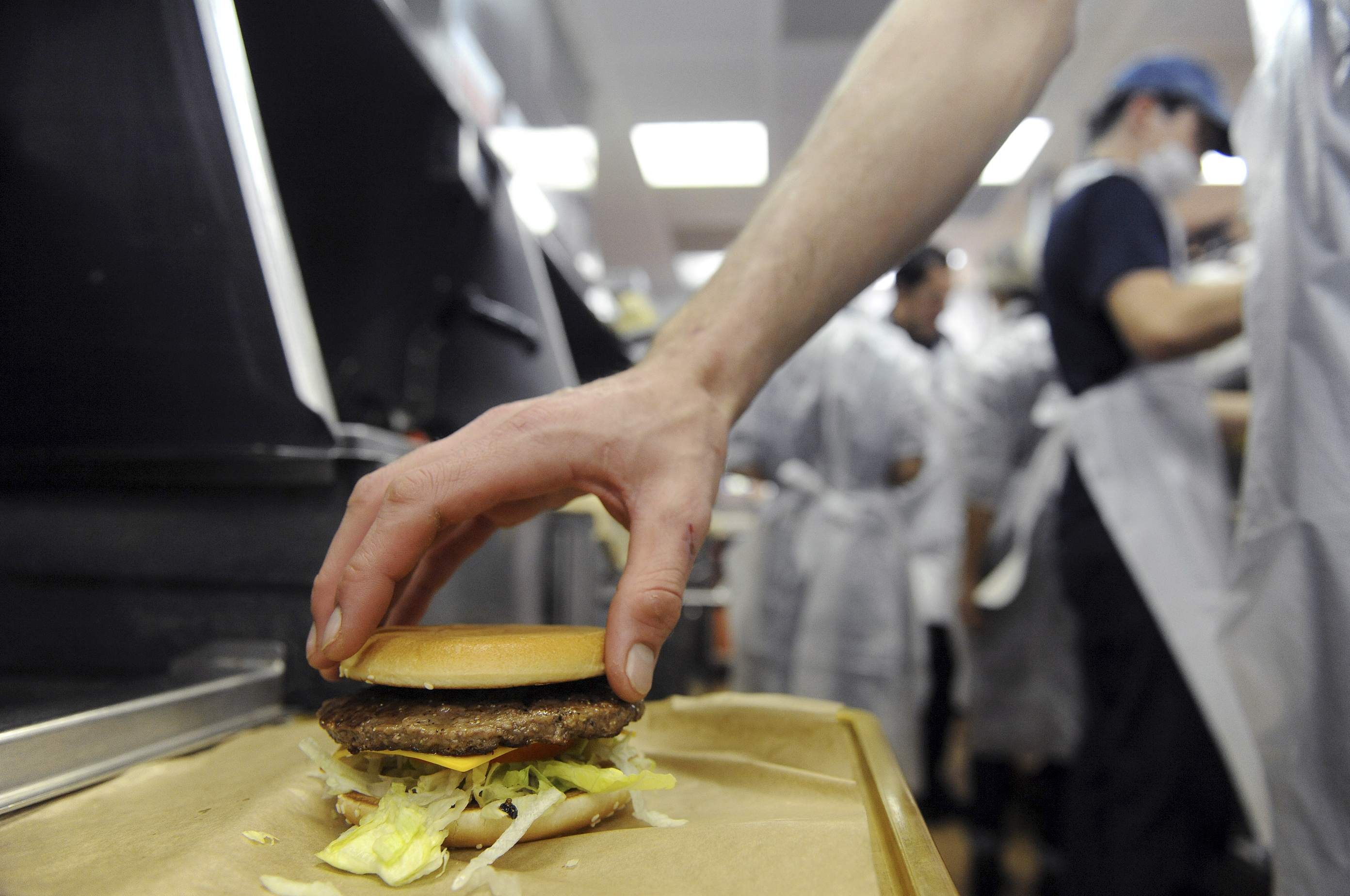 An employee prepares a hamburger at a US