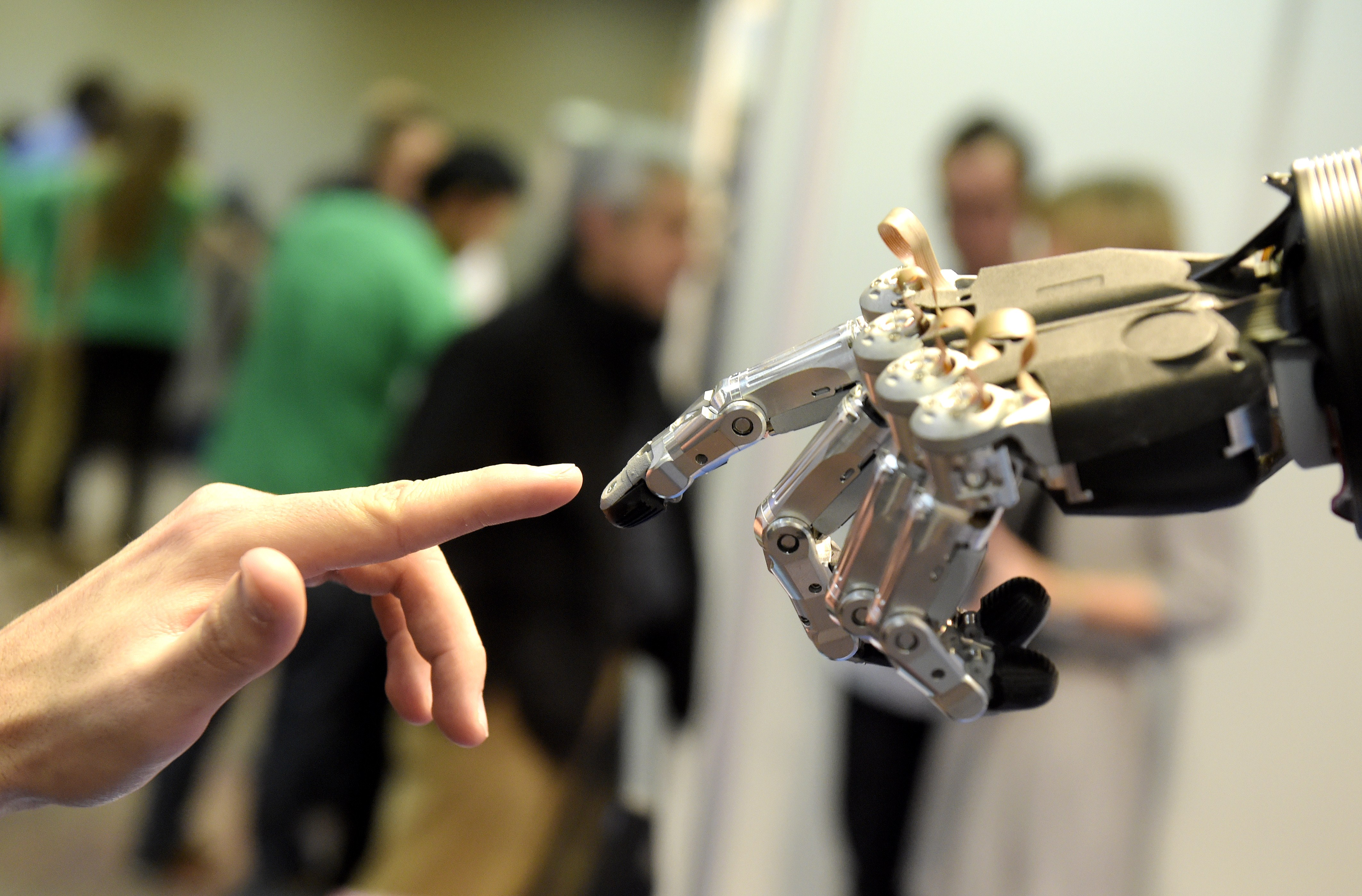 A man moves his finger toward SVH (Servo Electric 5 Finger Gripping Hand) automated hand made by Schunk during the 2014 IEEE-RAS International Conference on Humanoid Robots in Madrid on November 19, 2014.