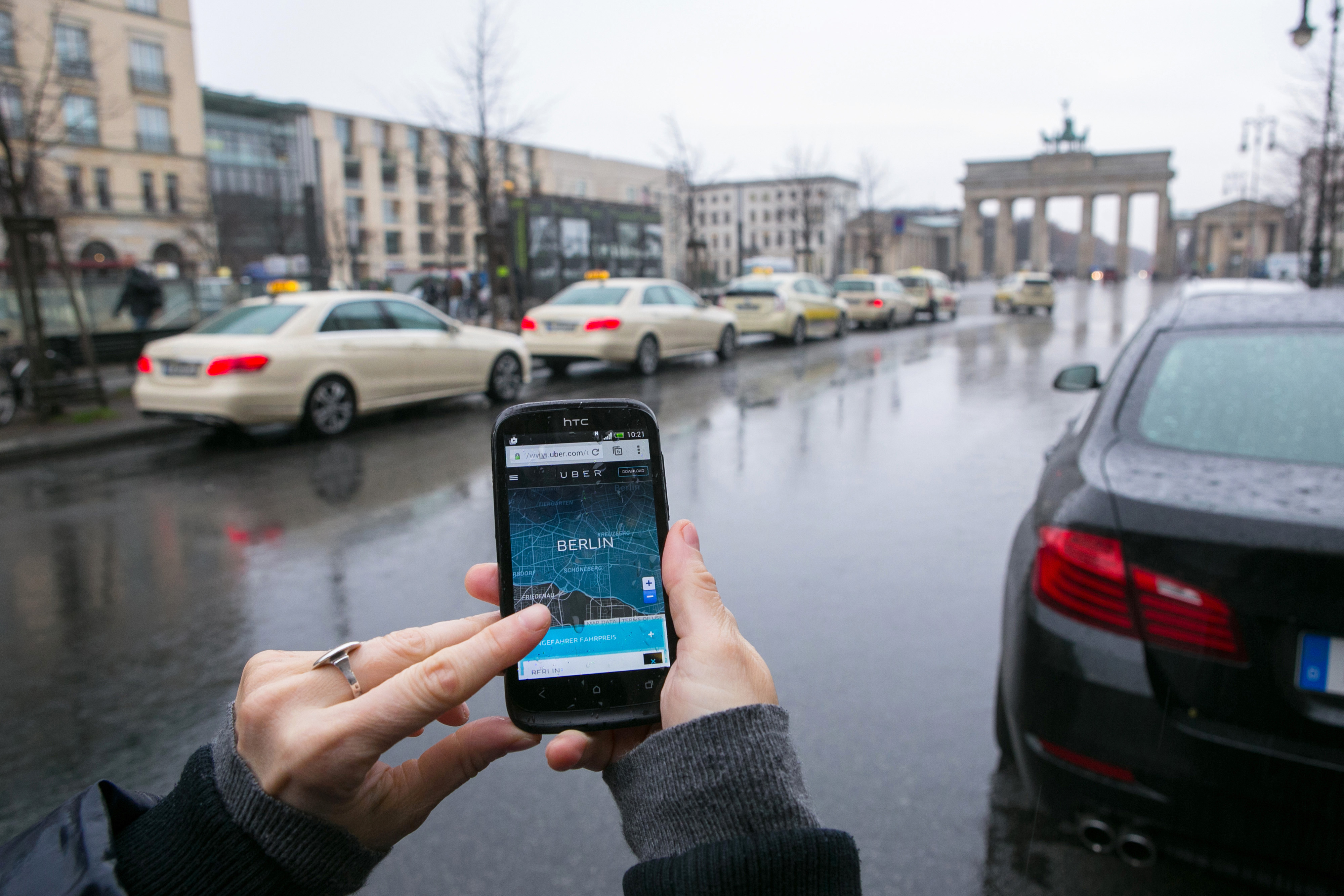 Uber is reducing the number of vehicles operating in two German cities during non-peak hours as the car-sharing service struggles with legal challenges.