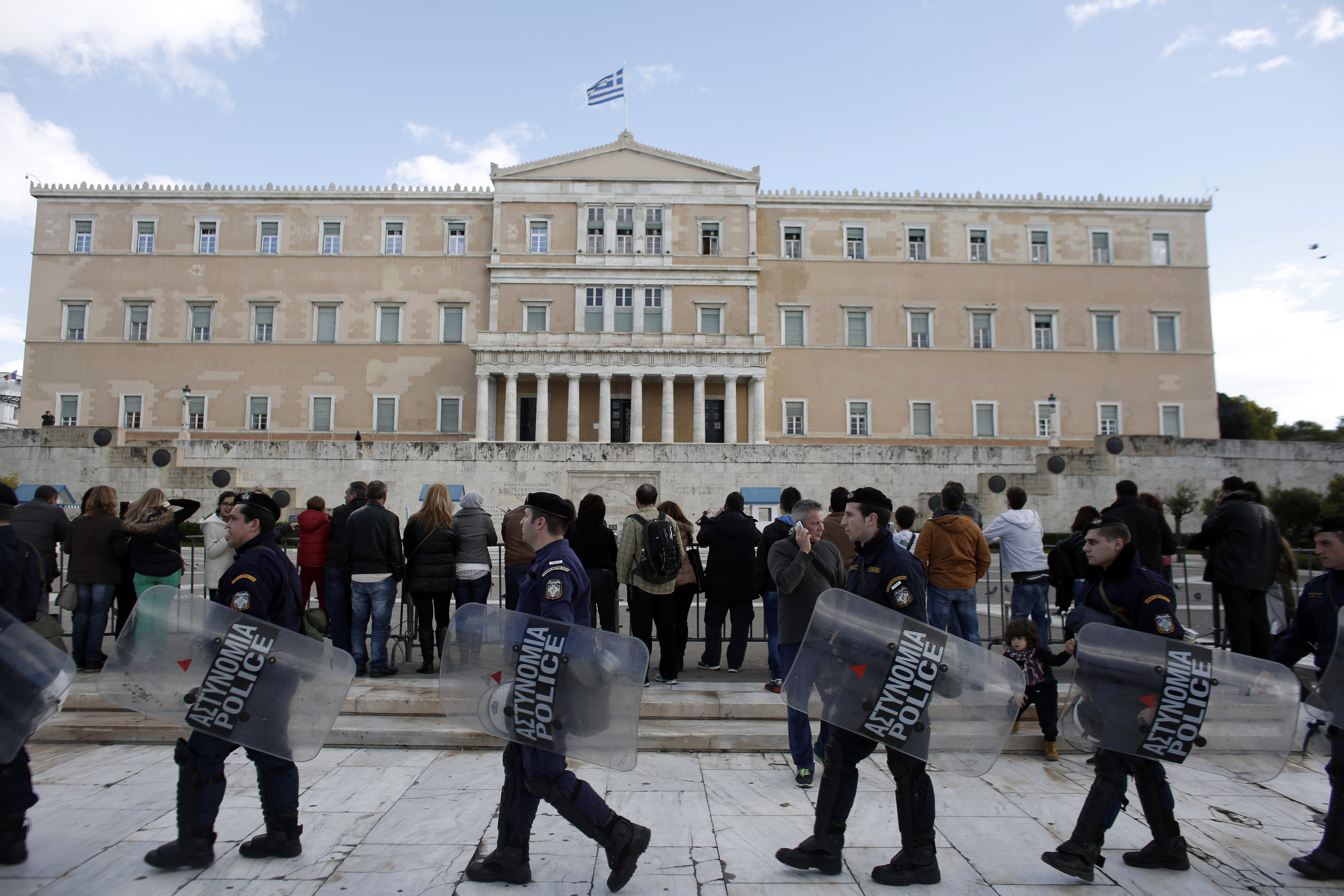 Riot police carry shields past tourists outside the parliament following a final vote by lawmakers for a new Greek president in Athens, Greece, on Monday, Dec. 29, 2014. Greece faces snap elections next month after Prime Minister Antonis Samaras failed in his third and final attempt to persuade parliament to back his candidate for head of state. Photographer: Kostas Tsironis/Bloomberg