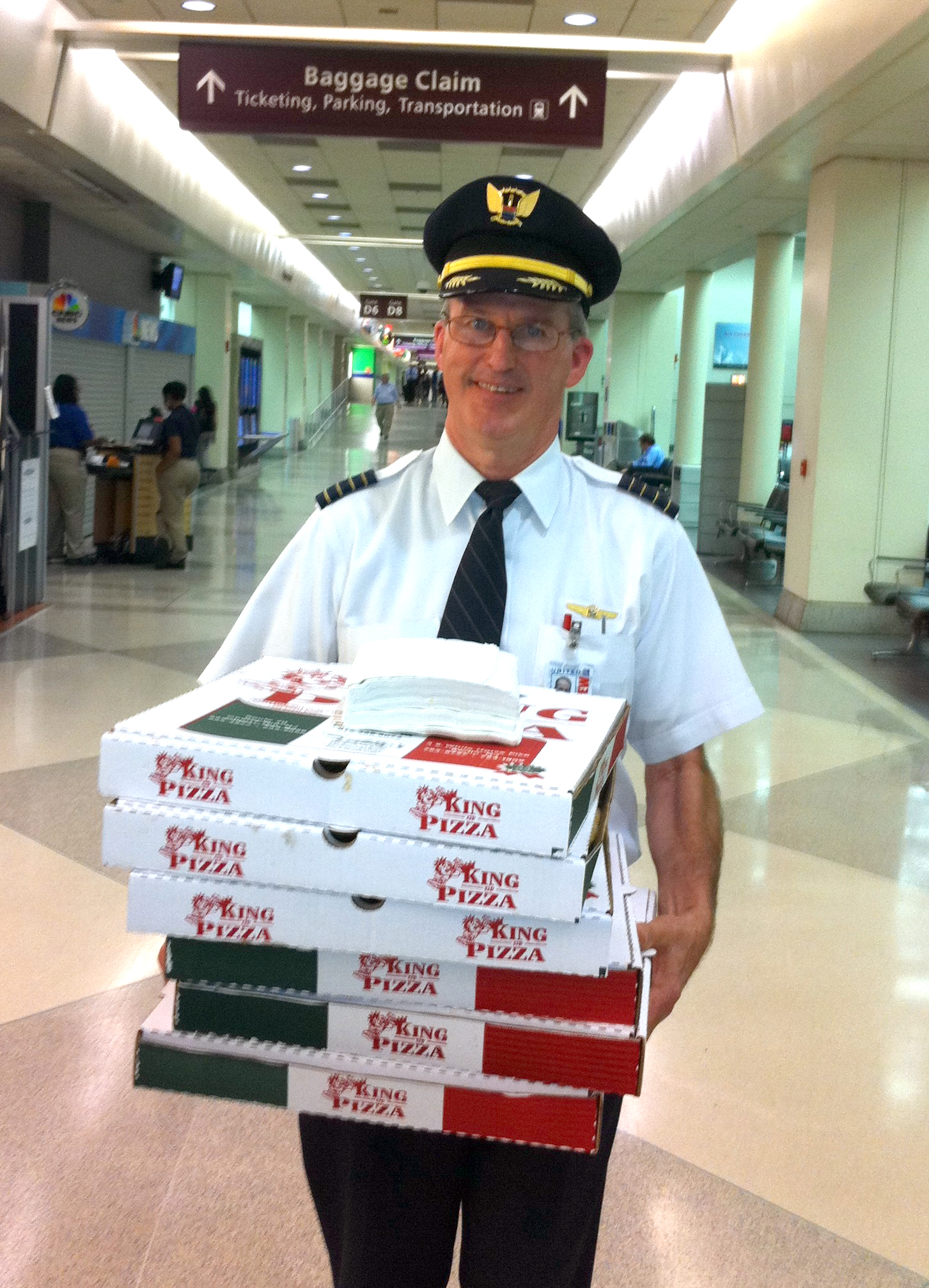 Capt. Denny Flanagan delivers pizza to delayed passengers in Philadelphia in December 2013.  Photo courtesy of United Airlines.
