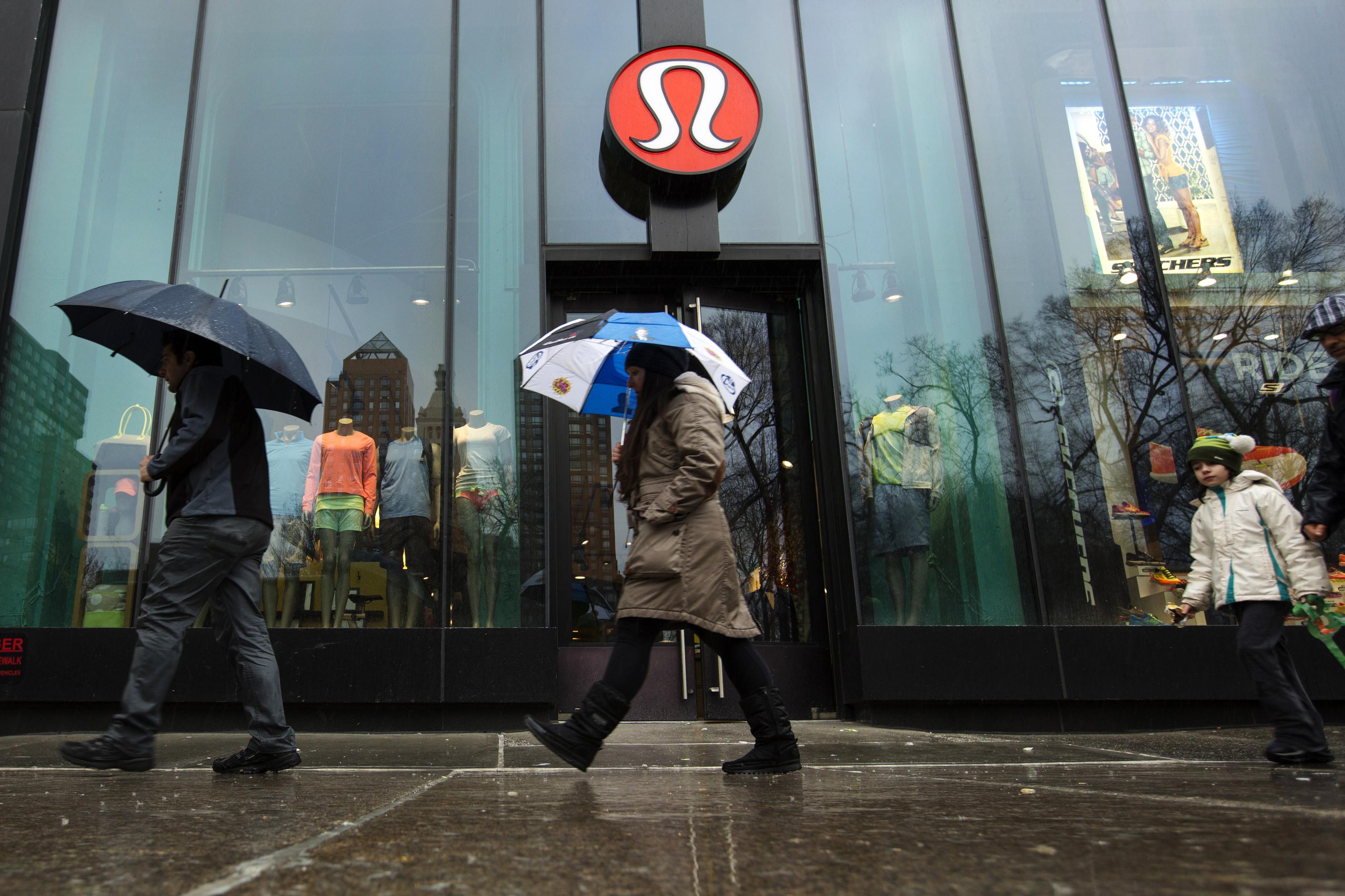 Pedestrians walk past a Lululemon Athletica store in New York