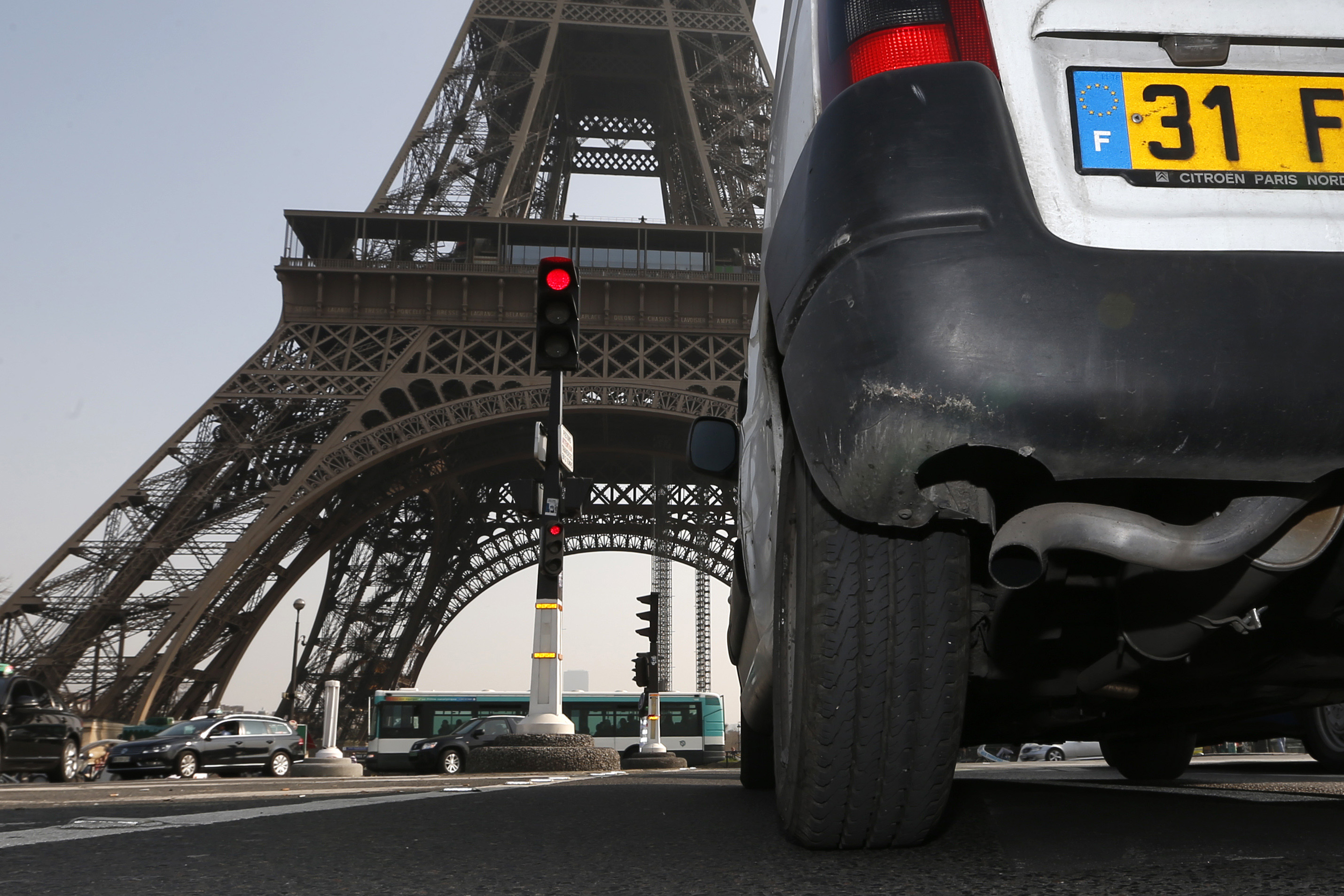 A car drives near the Eiffel tower in Paris during unusually high levels of pollution in France