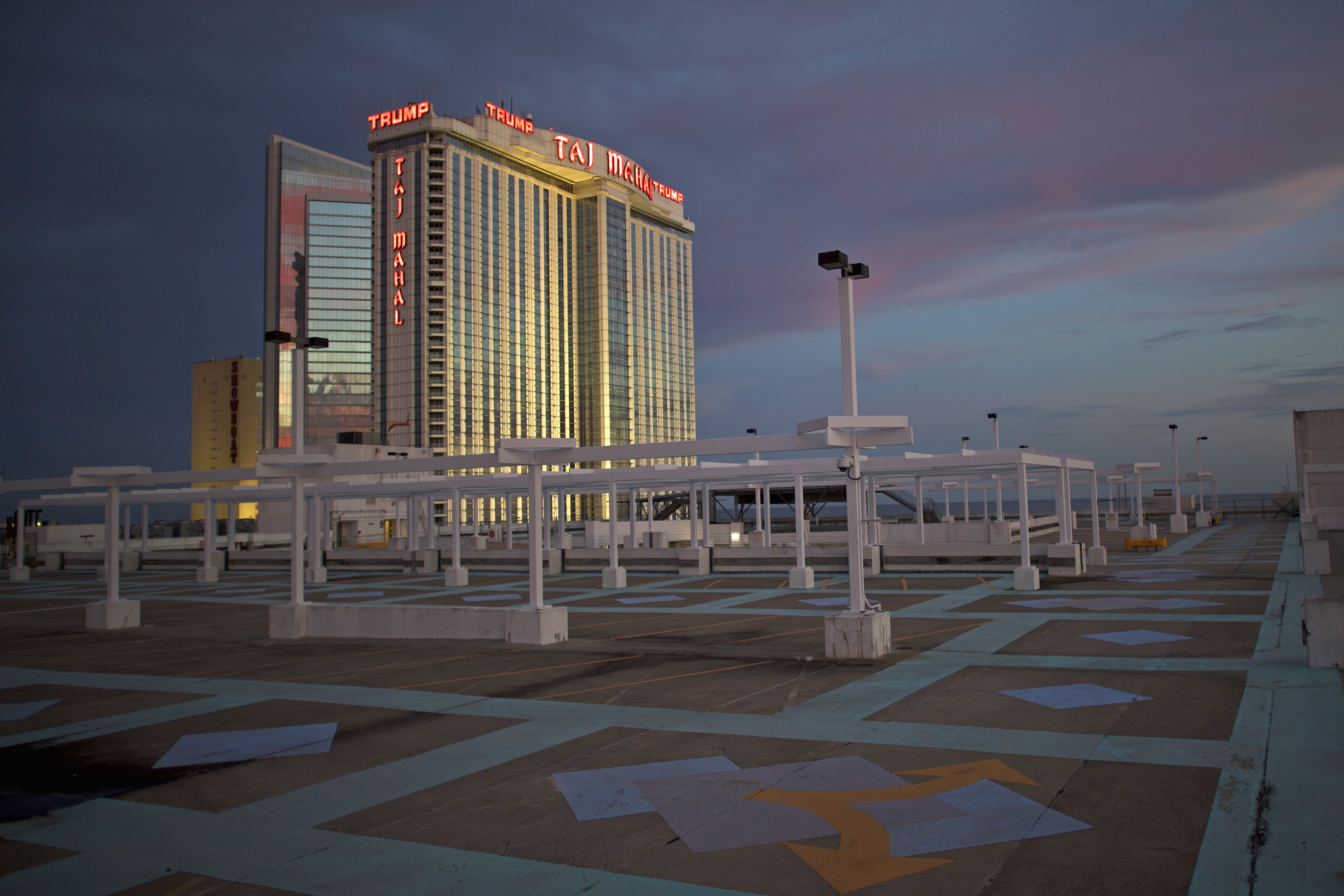 The illuminated Trump Taj Mahal Casino is seen from an empty rooftop parking lot at dusk in Atlantic City, New Jersey