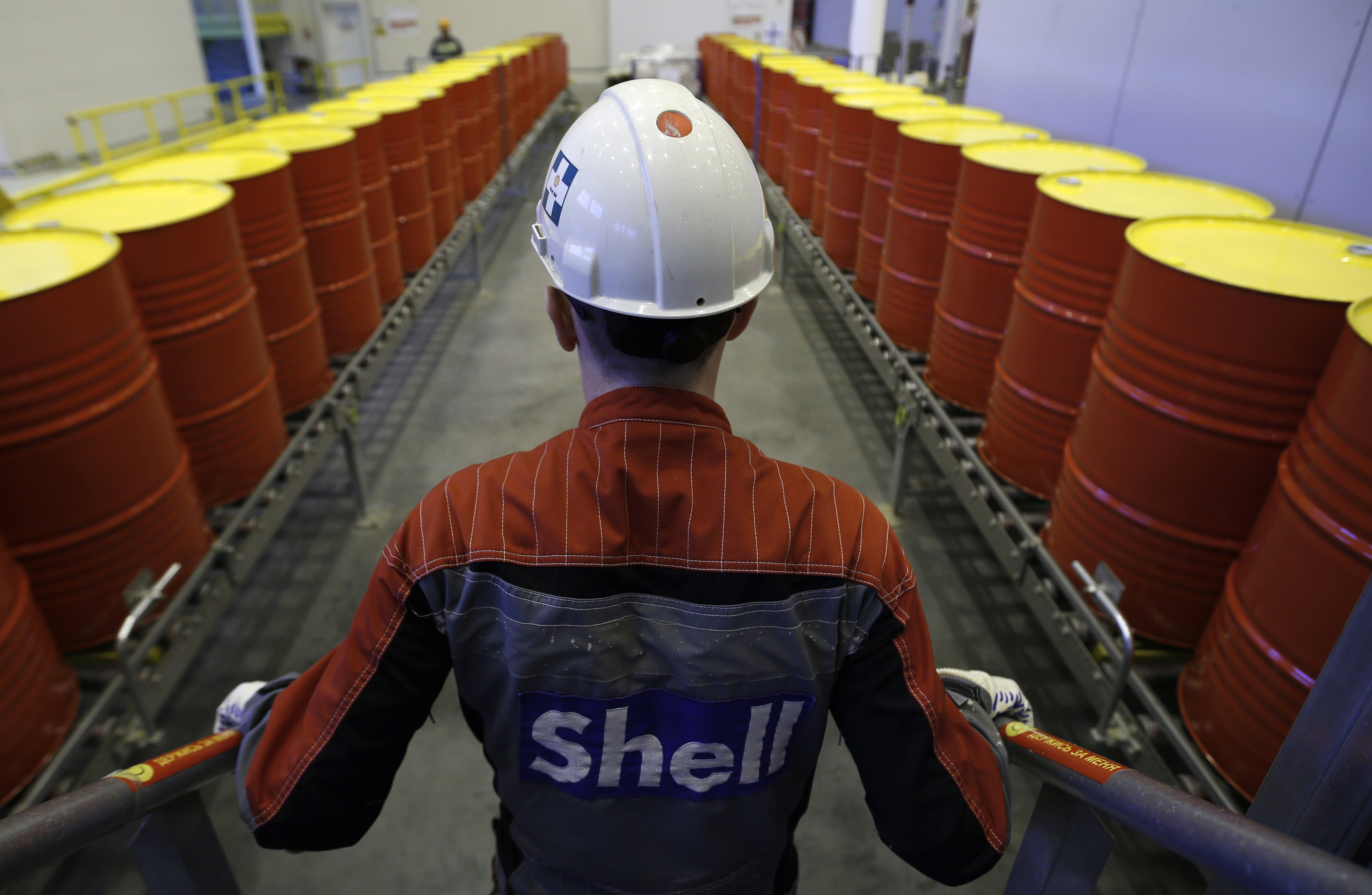 An employee stands in front of lines of oil barrels at Royal Dutch Shell Plc's lubricants blending plant in the town of Torzhok