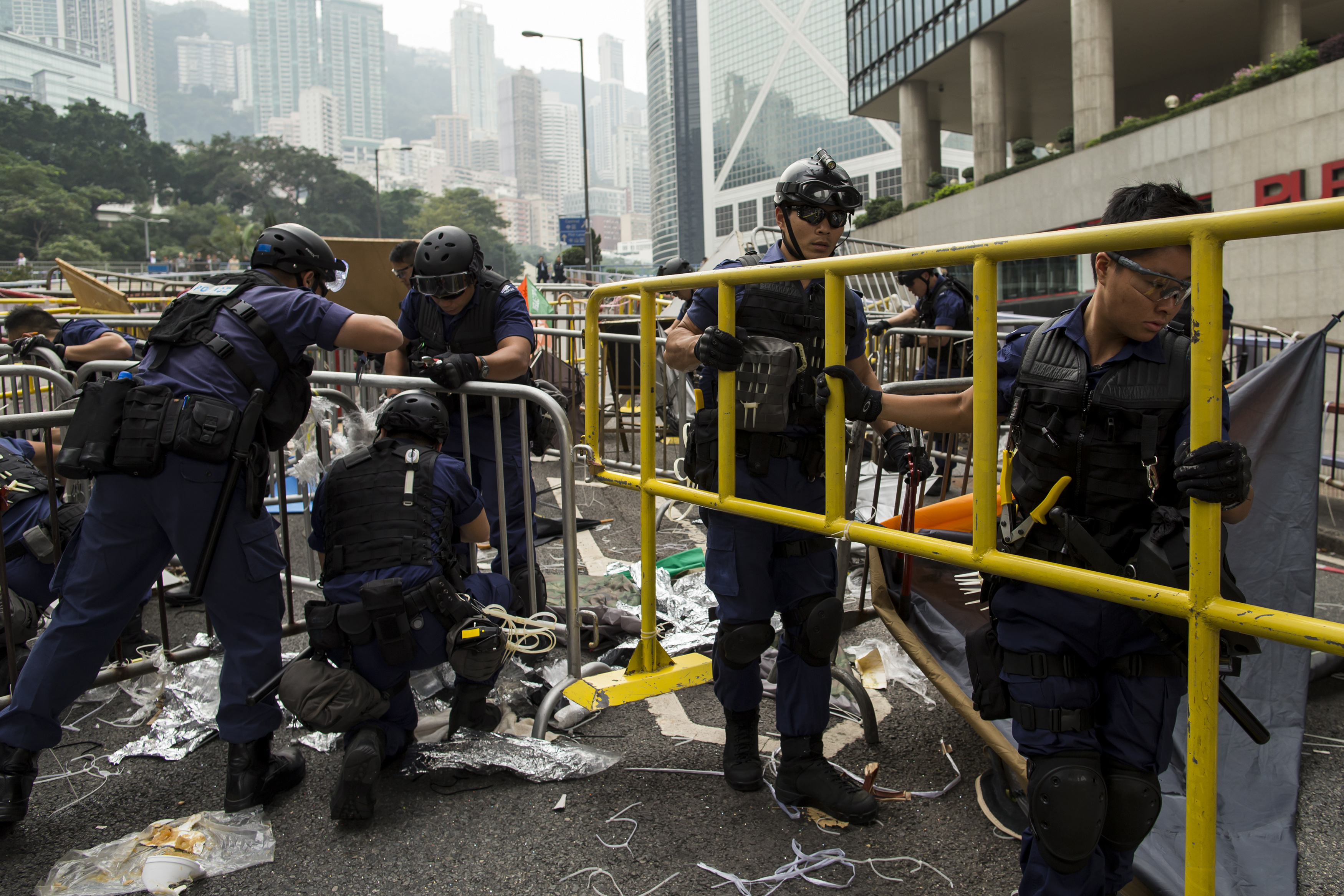 Police officers remove barricades at an area previously blocked by pro-democracy supporters near the government headquarters building at the financial Central district in Hong Kong