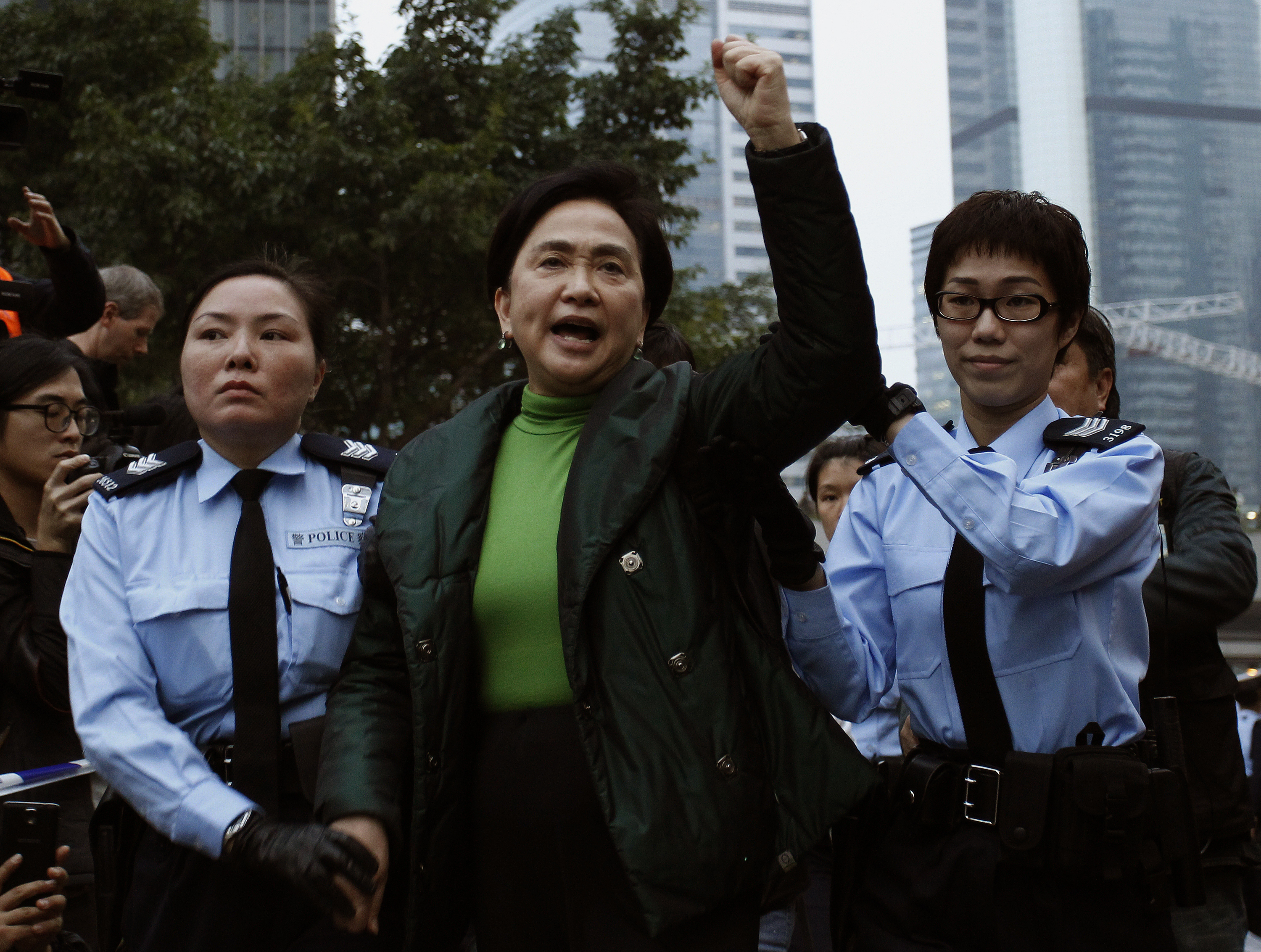 Pro-democracy lawmaker Emily Lau chants slogans as she is taken away by the police outside the government headquarters in Hong Kong